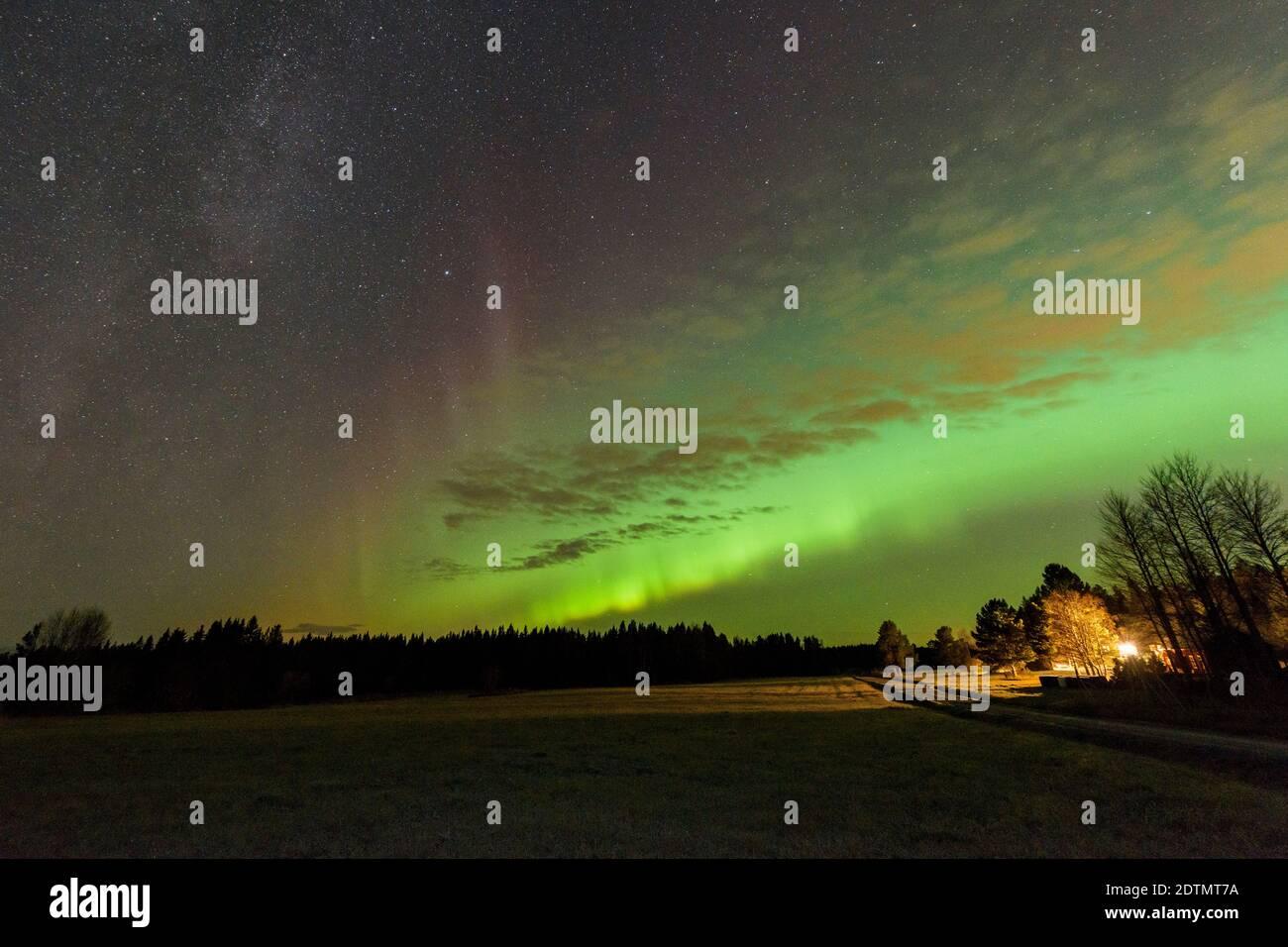 Vista escénica del campo contra el cielo de Aurora por la noche Foto de stock