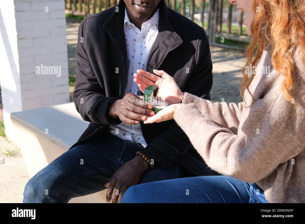 Un hombre negro africano irreconocible que le pide la mano a su novia caucásica de pelirroja. Propuesta de matrimonio. Foto de stock