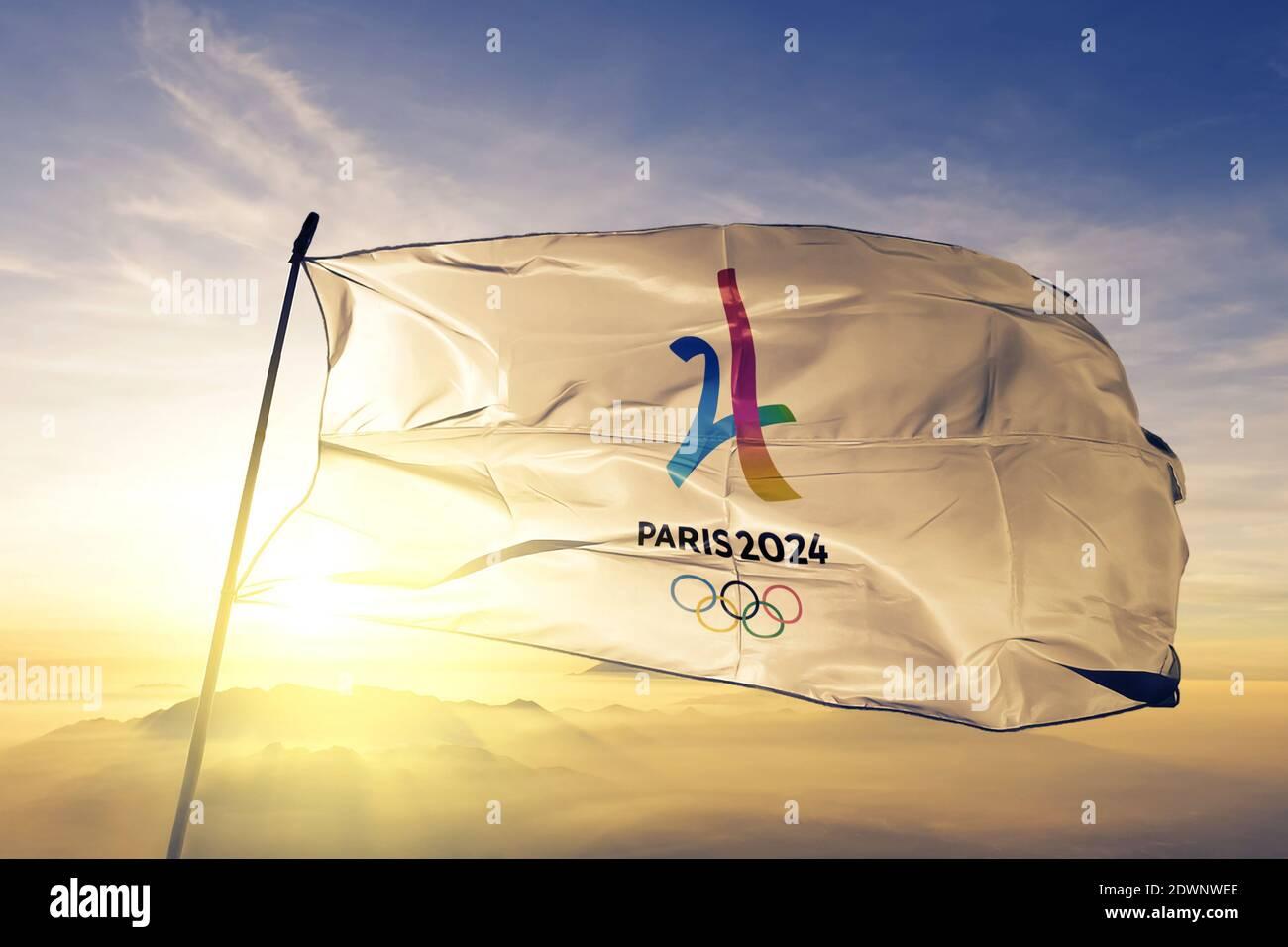 2024 bandera del logo de los Juegos Olímpicos de Verano ondeando en la salida del sol superior niebla Foto de stock