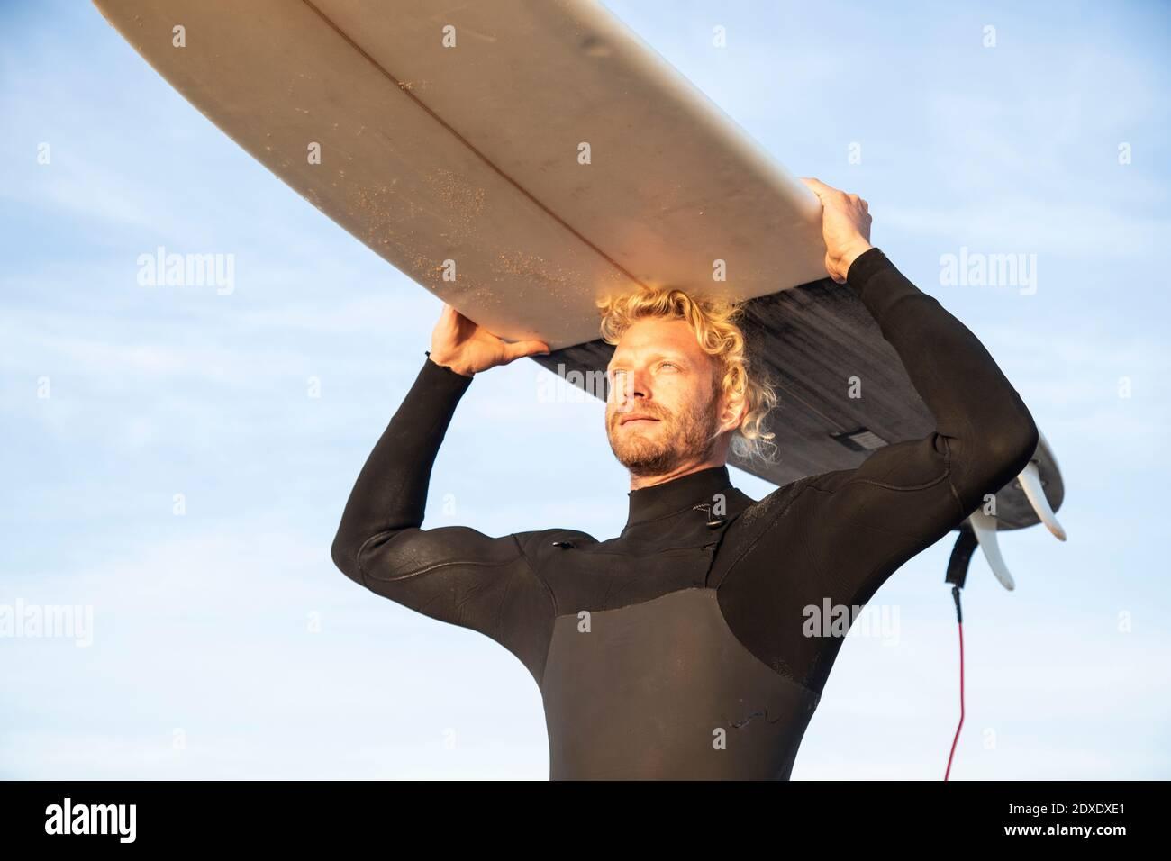 Surfista rubio masculino llevando tabla de surf sobre la cabeza en la playa contra cielo Foto de stock