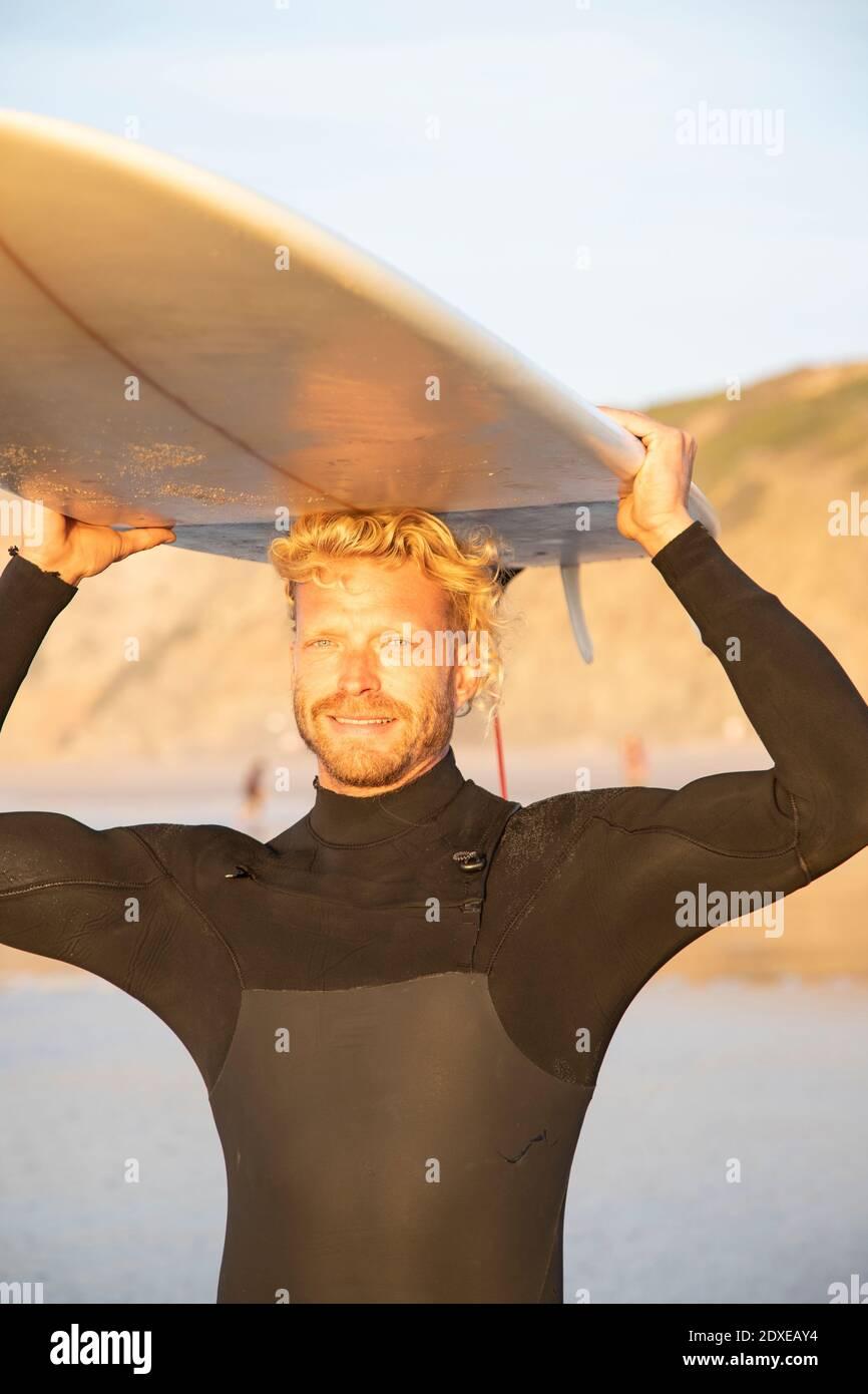 Hombre rubio sonriente llevando tabla de surf sobre la cabeza en la playa durante puesta de sol Foto de stock