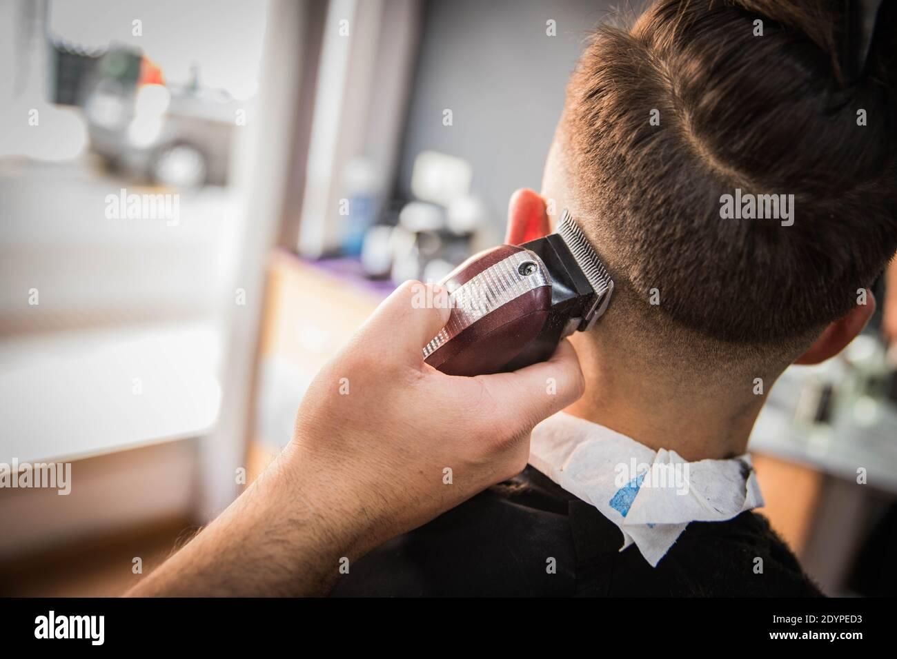 Primer plano de la mano de un barbero que está cortando el pelo a. un cliente en su casa de peluquero Foto de stock