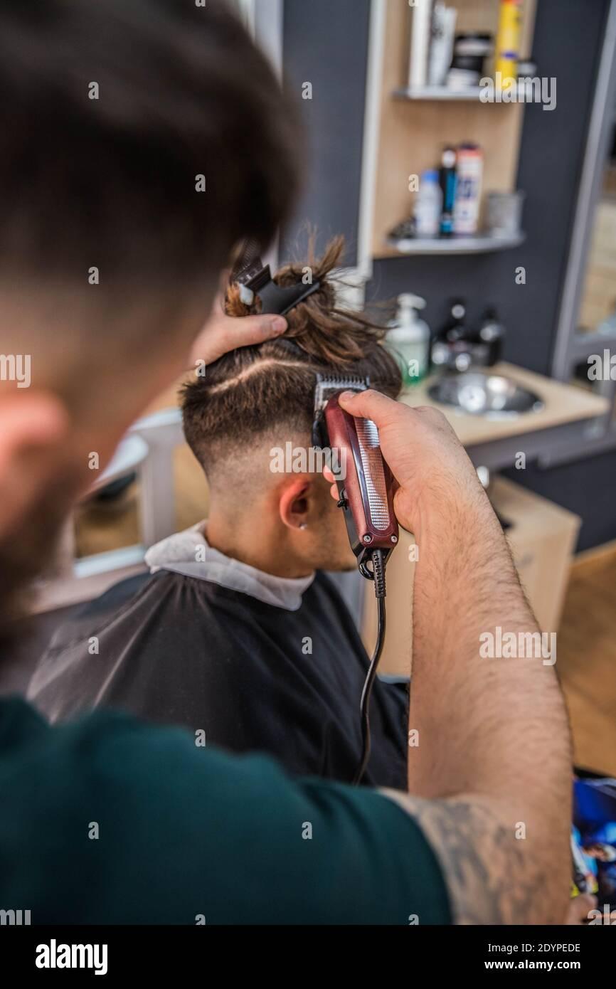 Barber cortando el pelo a su joven cliente con su cortapatillas Foto de stock