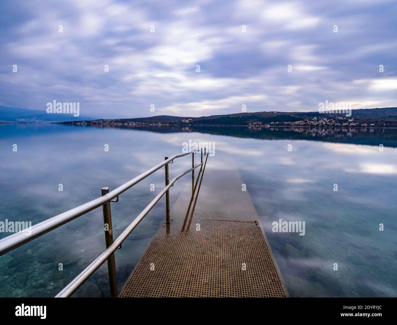 Barandilla de la valla metálica que conduce al mar de exposición larga Cizici En la isla de Krk en Croacia Europa la exposición prolongada refleja suave calma superficie calma Foto de stock