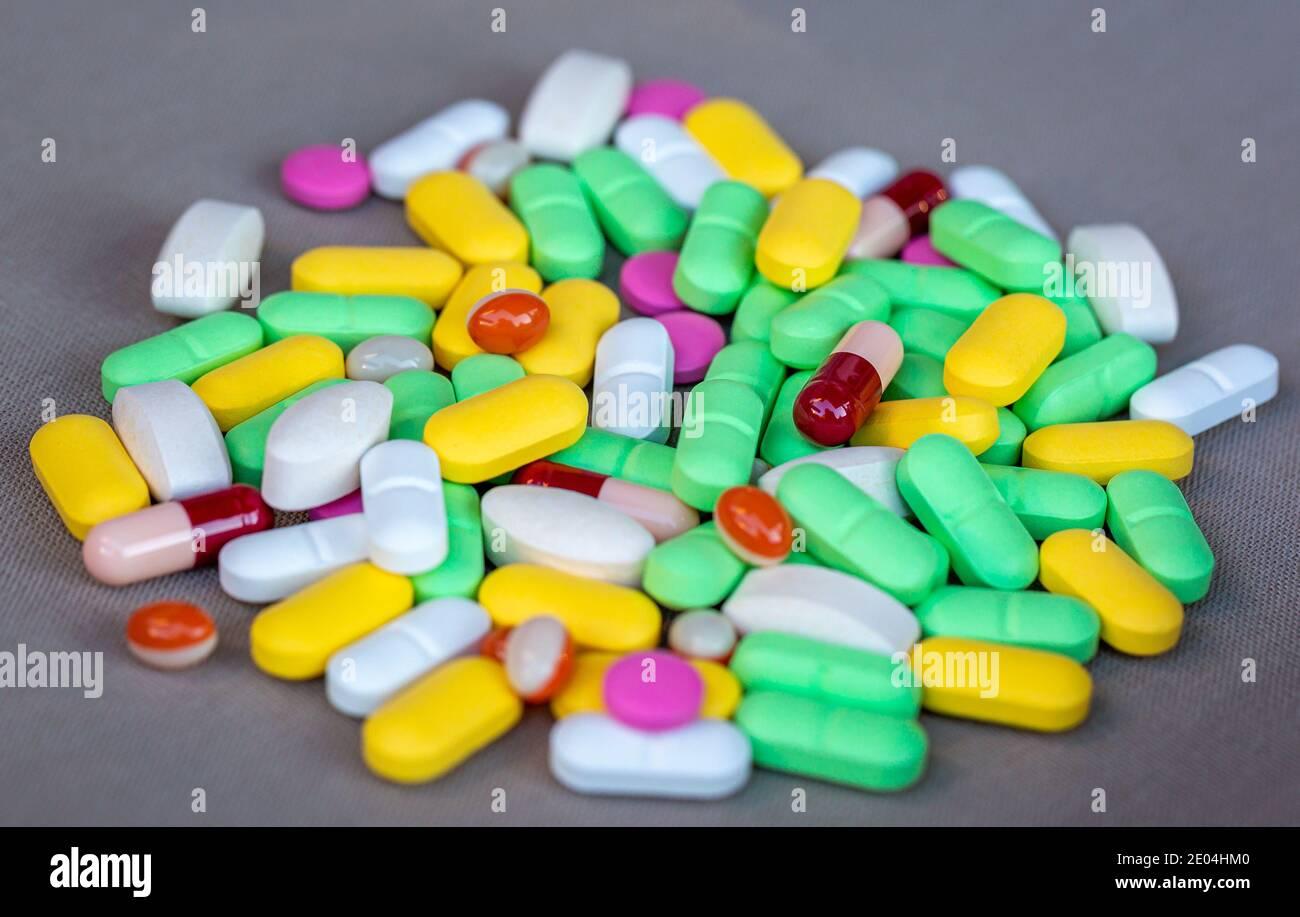 Montón de pastillas y cápsulas de varios colores sobre fondo gris . Enfoque superficial. Foto de stock