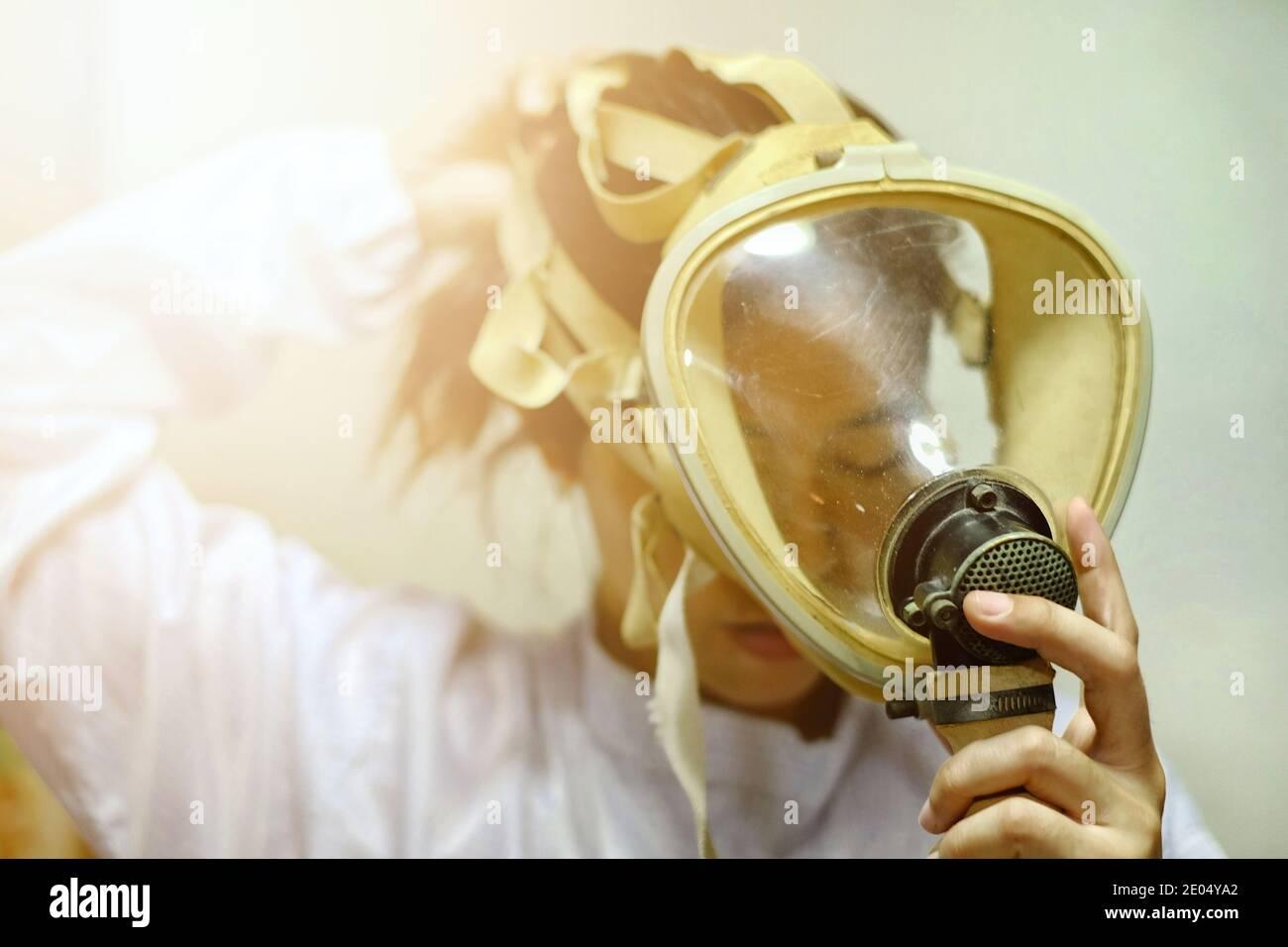 Una mujer asiática que tira de una máscara de oxígeno protector de cara completa, abrigo blanco y guantes de goma, preparándose para trabajar en un laboratorio bioquímico. Foto de stock