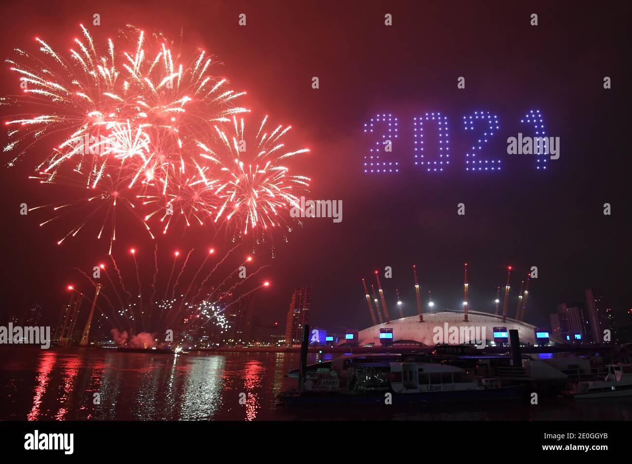 Los fuegos artificiales y los aviones teledirigidos iluminan el cielo nocturno sobre el O2 en Londres, ya que forman una pantalla de luz, ya que el despliegue normal de fuegos artificiales de la víspera de año Nuevo de Londres fue cancelado debido a la pandemia del coronavirus. Foto de stock