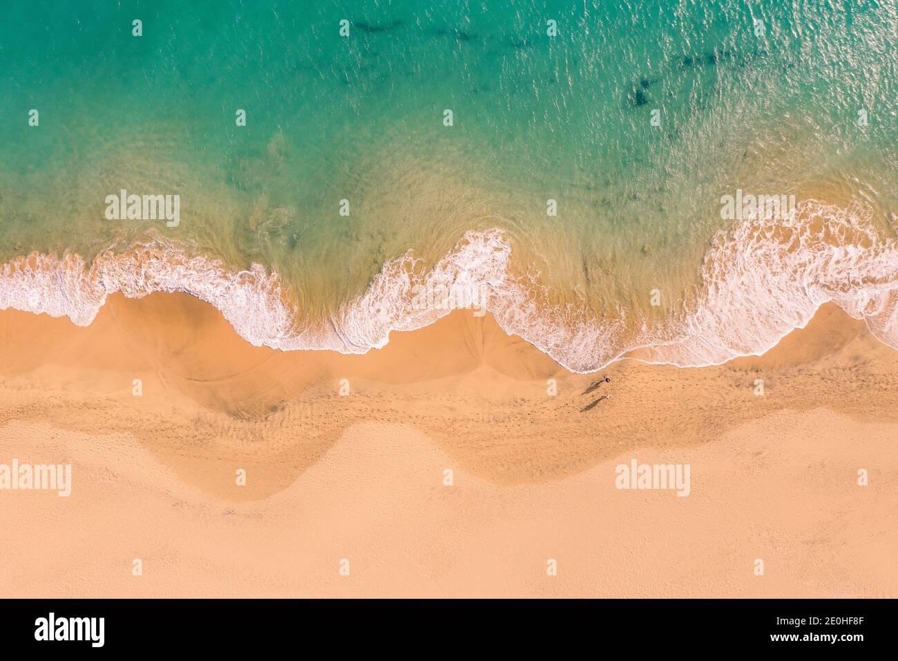 Vista aérea de arriba hacia abajo de la hermosa costa del océano Atlántico con aguas cristalinas color turquesa y playa de arena, olas que ruinan en la costa Foto de stock