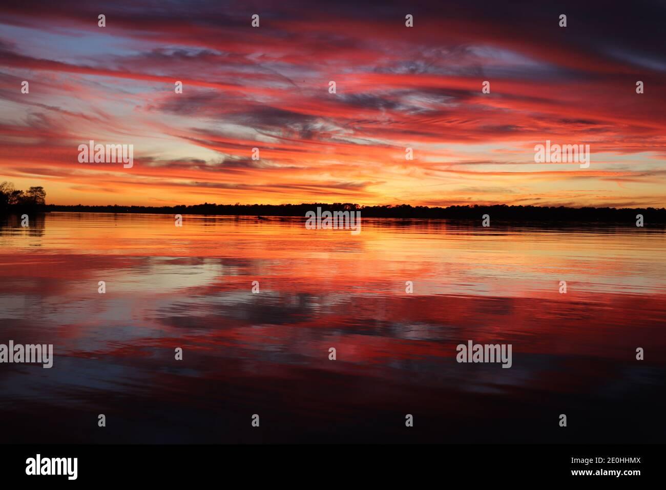 Puesta de sol con reflejos de espejo en la superficie del agua. Vibrantes colores de remolinos rojos y dorados desde el cielo azul hasta el tranquilo horizonte arbolado. Foto de stock