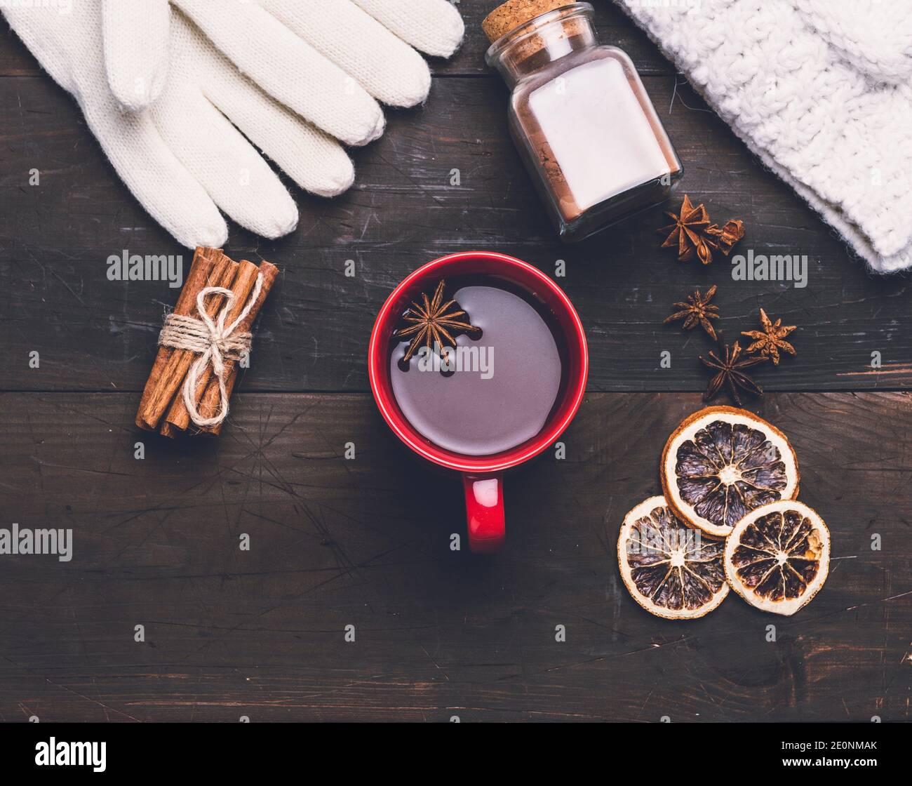 manoplas de punto y copa roja con una bebida en una mesa de madera marrón, vista superior. Foto de stock