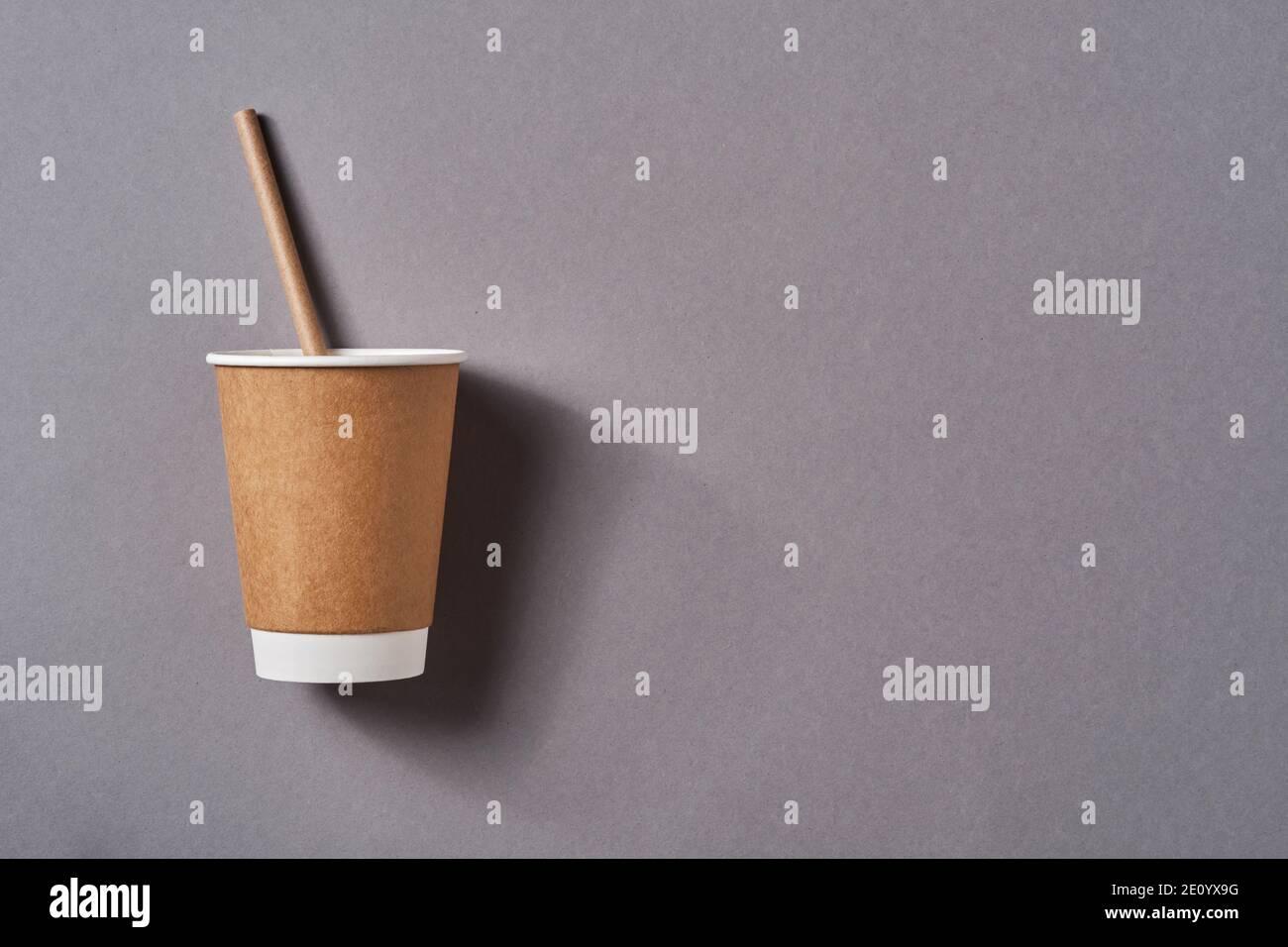 Taza de café para llevar marrón con papel de paja potable sobre fondo de color gris tendencia. Cero desperdicio, concepto de estilo de vida sostenible. Vista superior Foto de stock