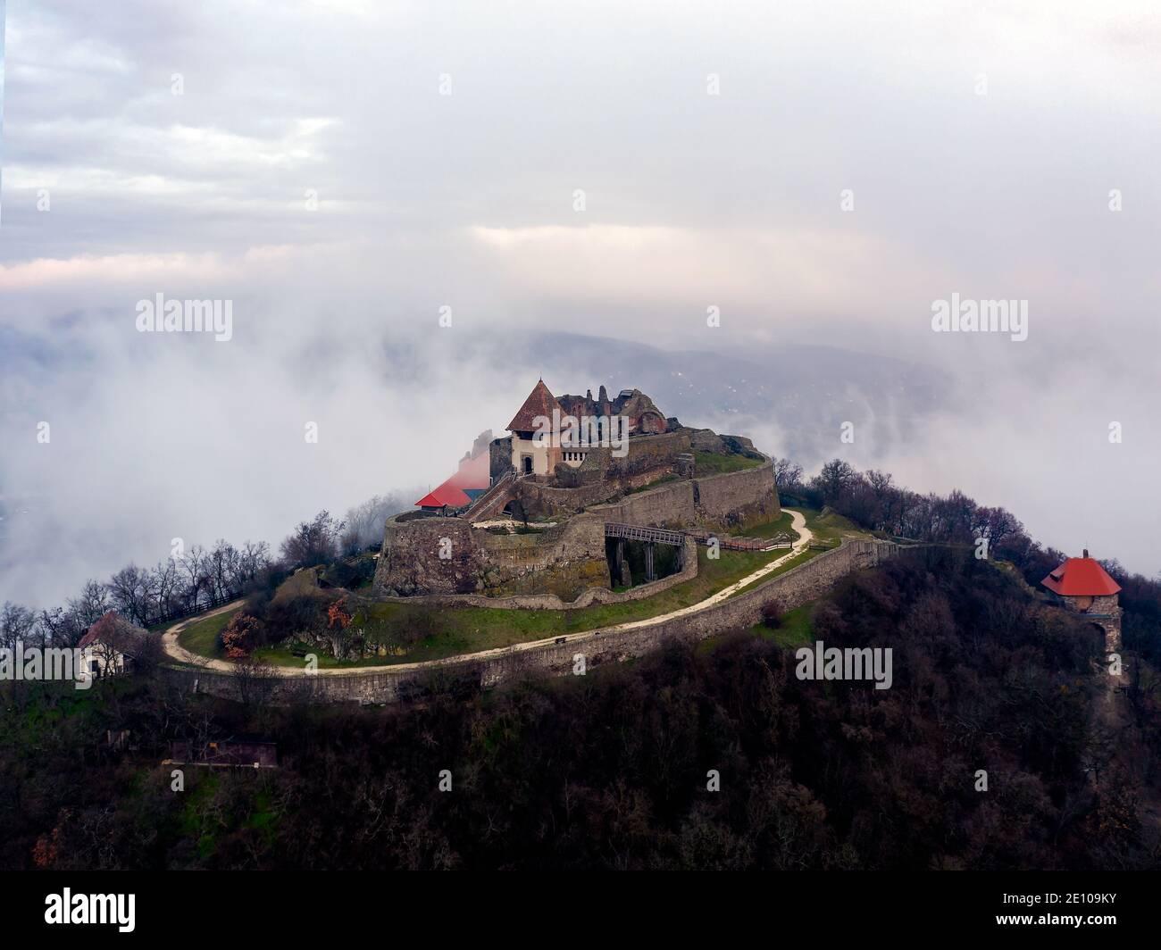Ruinas del castillo de la ciudadela de Visegrad en la curva del Danubio Hungría. Fantástico paisaje aéreo en mal tiempo. Un amanecer turbio y turbio Foto de stock