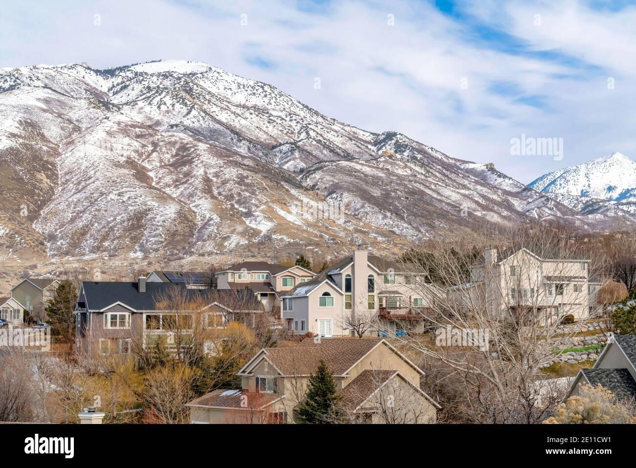 Montaña nevada y casas en un paisaje de barrio del Valle de Utah en invierno Foto de stock