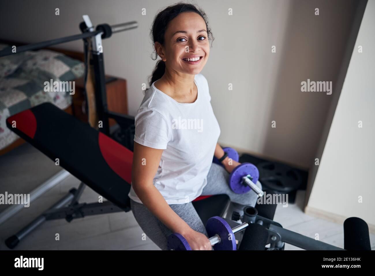 Culturista femenino con pesas sentado en el banco de entrenamiento Foto de stock