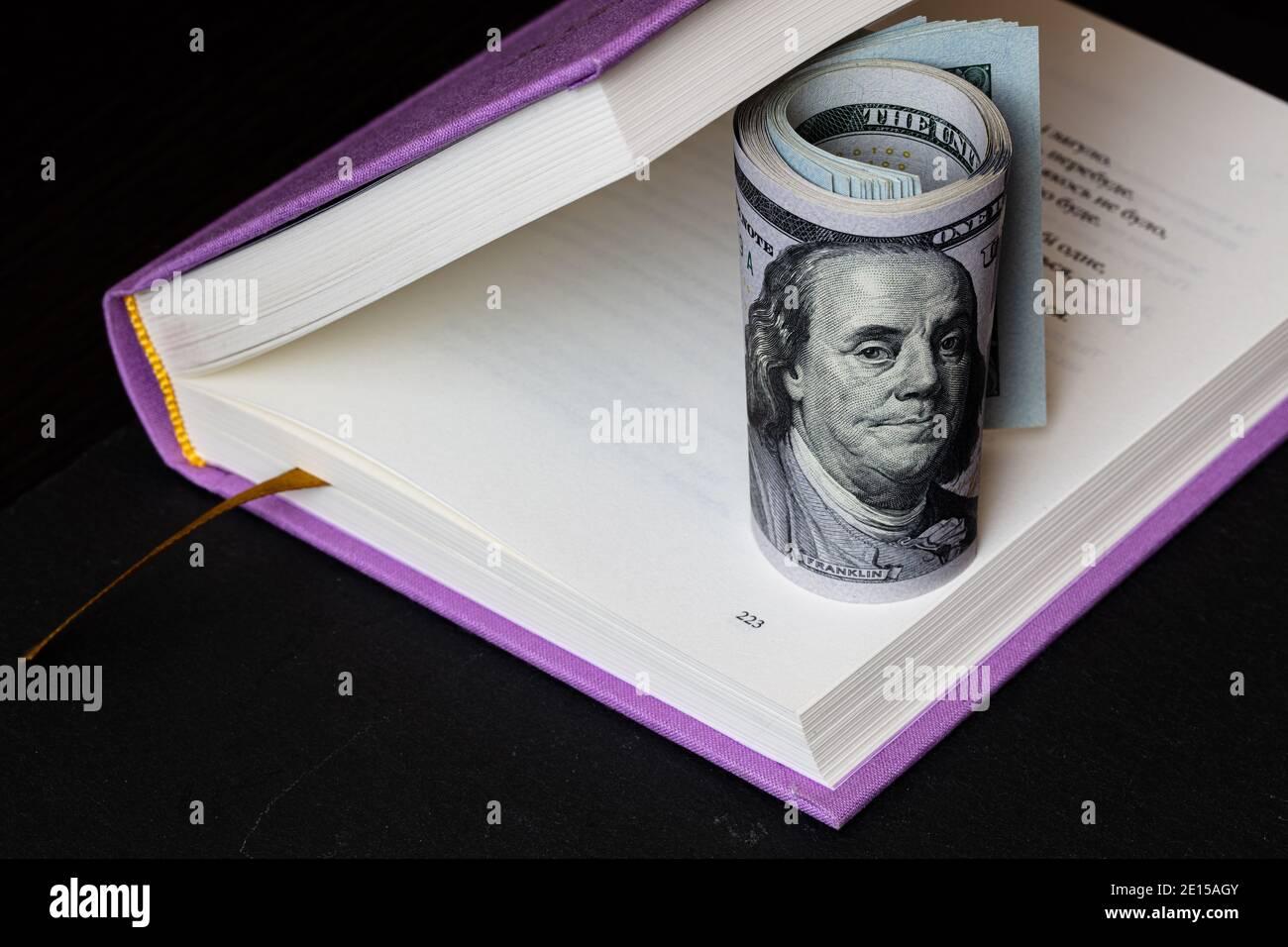 rollo de billetes de 100 dólares en libro violeta Foto de stock