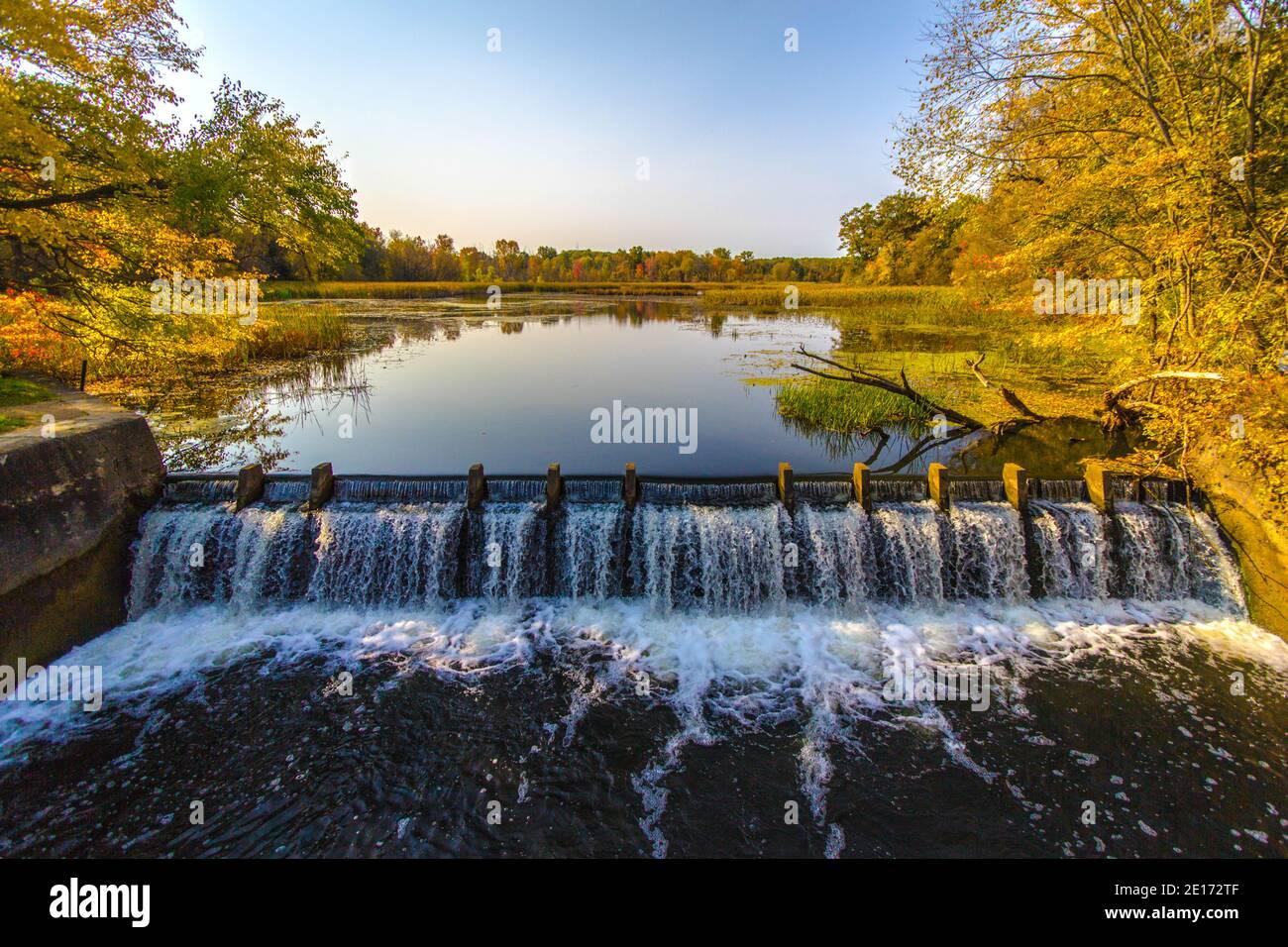 Presa en el río crea un hermoso humedal natural con árboles reflejados en el embalse. Foto de stock
