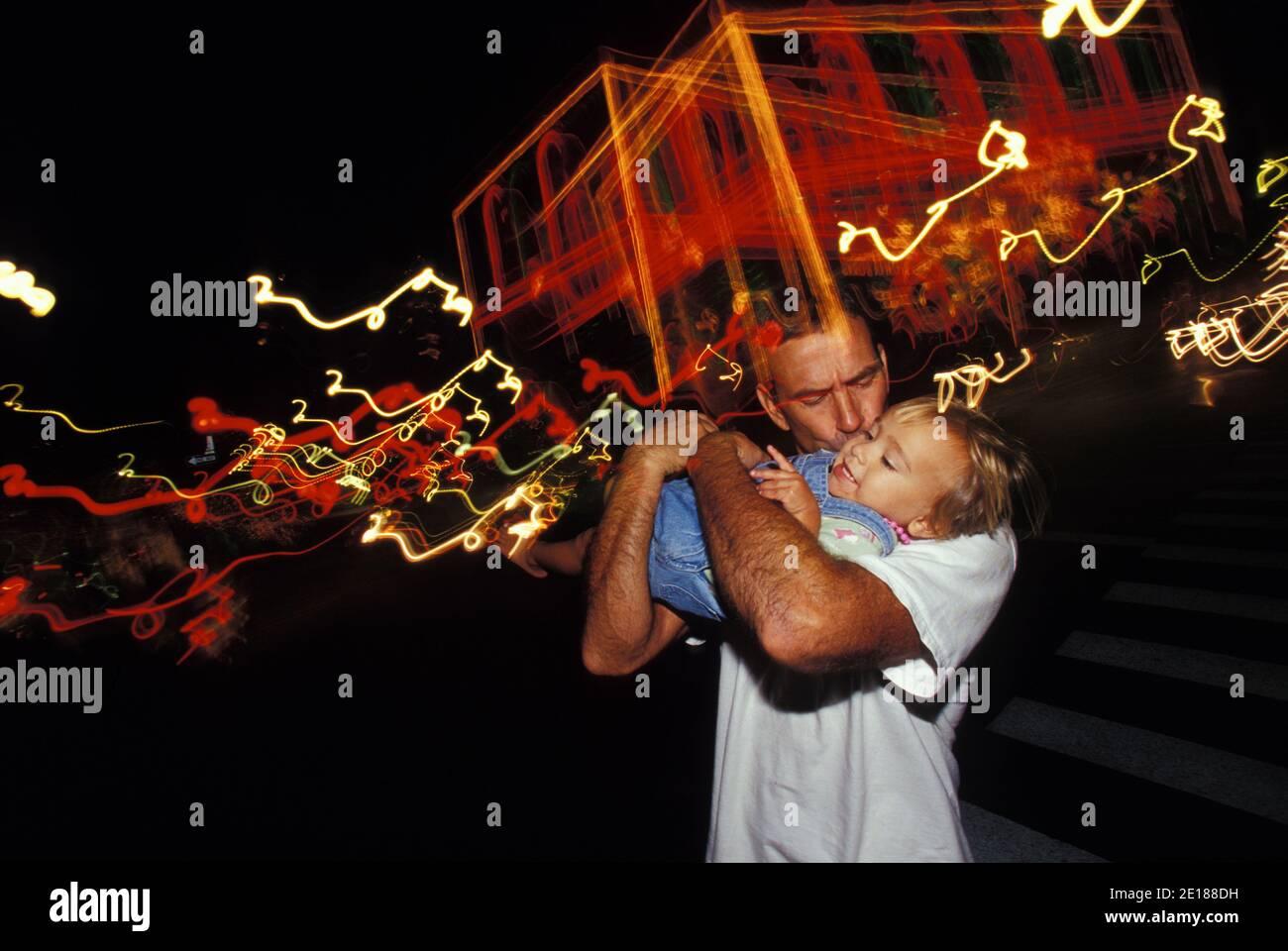 El padre besa a la hija cerca de las luces de Navidad en el centro de Honolulu Foto de stock
