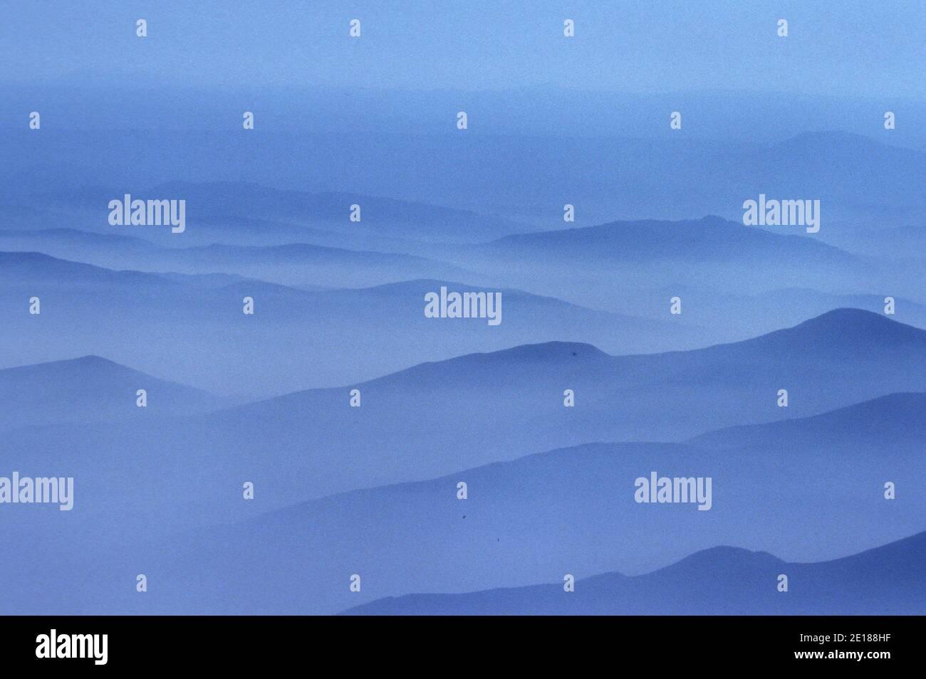 Misty nubes blancas por la mañana con crestas de montaña Foto de stock