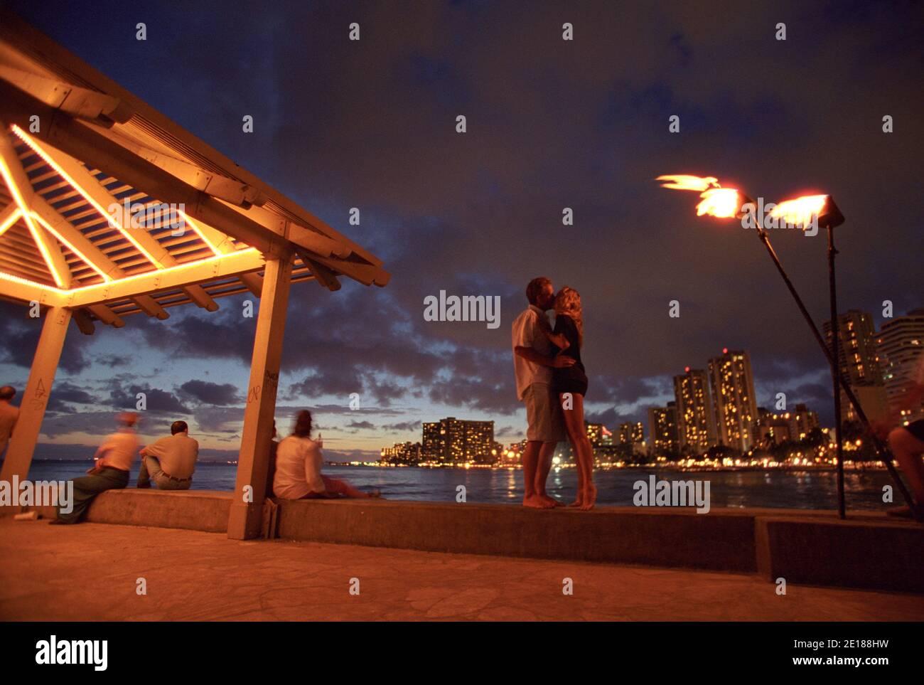 Pareja besando en un muelle en Waikiki al atardecer con antorchas tiki y luces de hotel en el fondo Foto de stock
