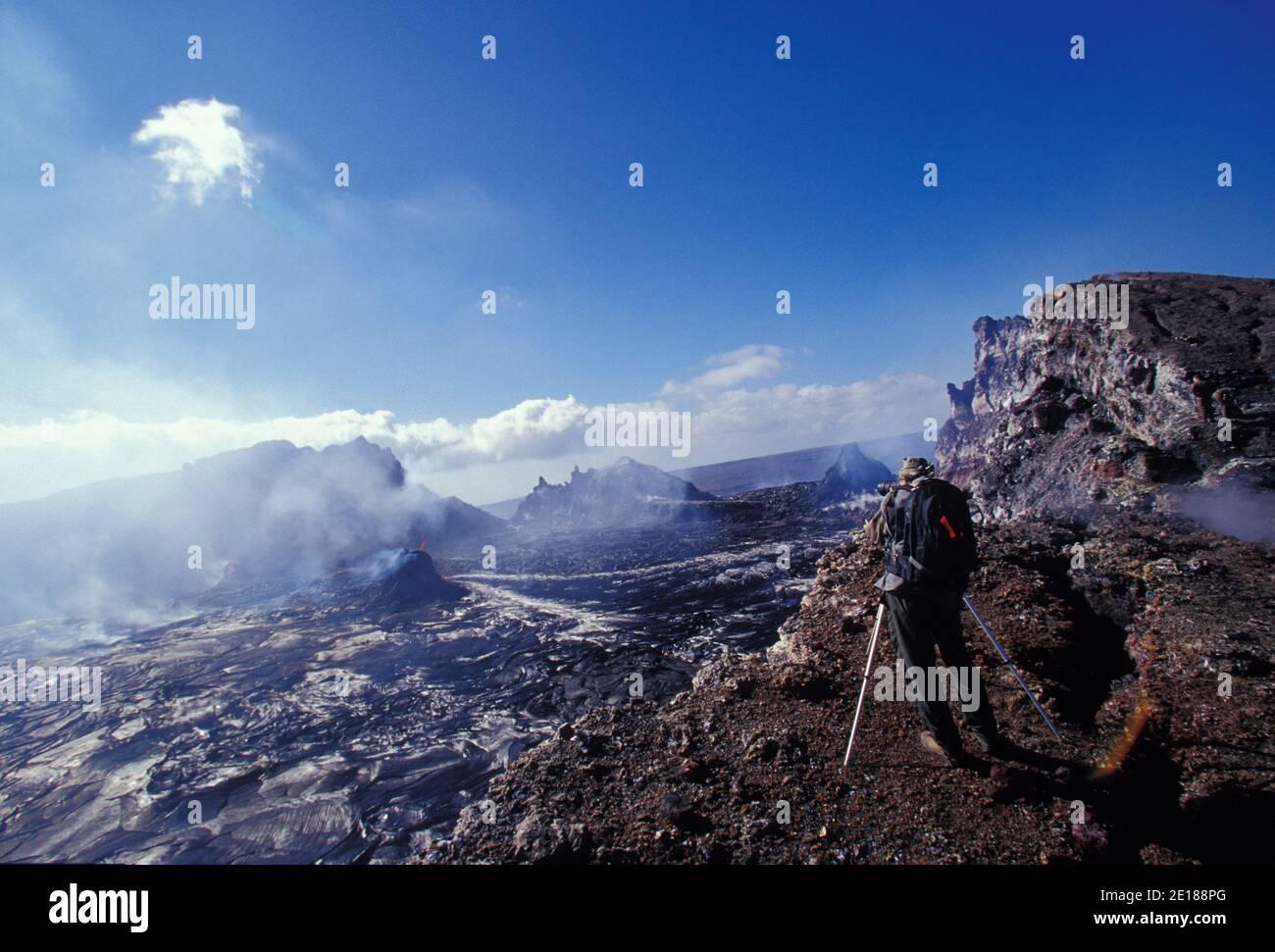 El veterano fotógrafo del volcán Brad Lewis filmando la erupción de Pu' o'o Caldera, Parque Nacional de los Volcanes Foto de stock