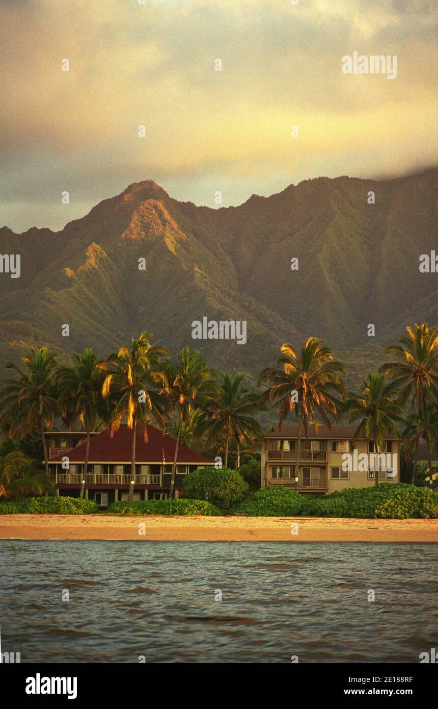 Casas de alquiler de vacaciones frente a la playa con Mt. Ka'ala en el fondo, disparado desde el mar, a la luz de la tarde, en Waialua, en la costa norte de Oahu Foto de stock