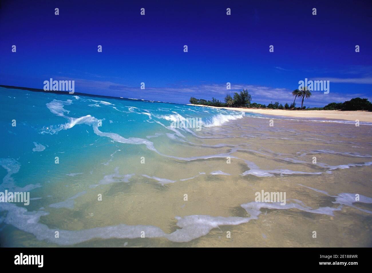 Waves breaking in clear blue water on white sand beach, Velzyland, North Shore, Oahu Foto de stock