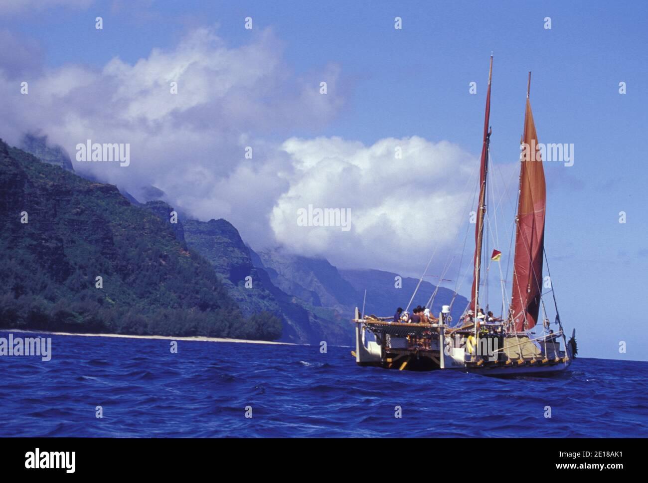 Hokulea, una tradicional canoa hawaiana de doble casco, zarpa de la costa Na Pali para el viaje a las islas hawaianas del noroeste Foto de stock