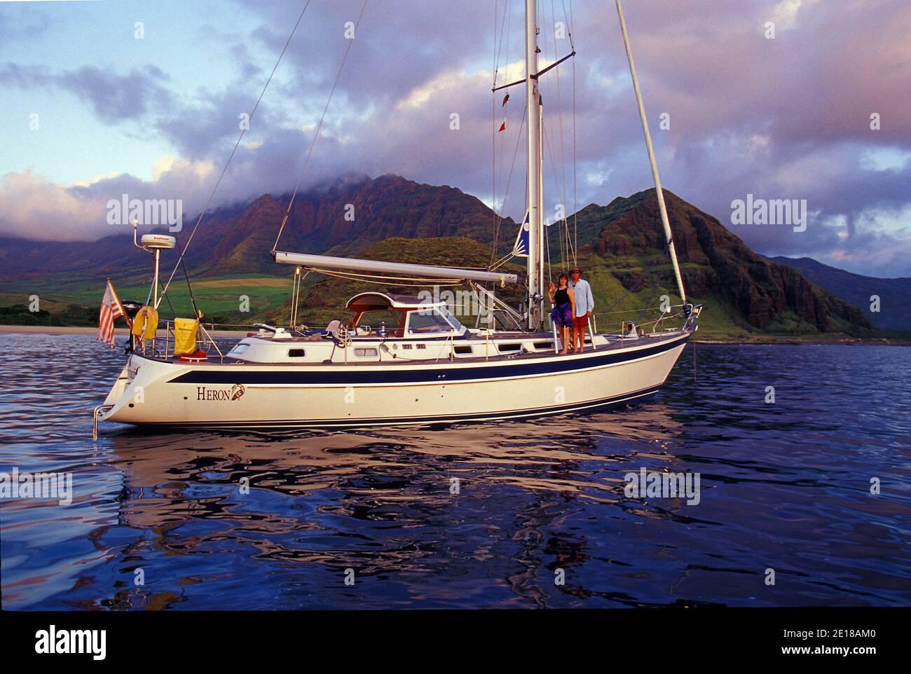 Couple on deck of their 48 foot sailboat off Makua Beach, West Oahu, Hawaii Foto de stock