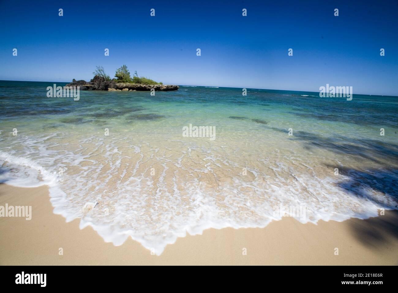 Escena de playa en una playa desierta de la costa norte con un pequeña isla costera en aguas azules claras Foto de stock