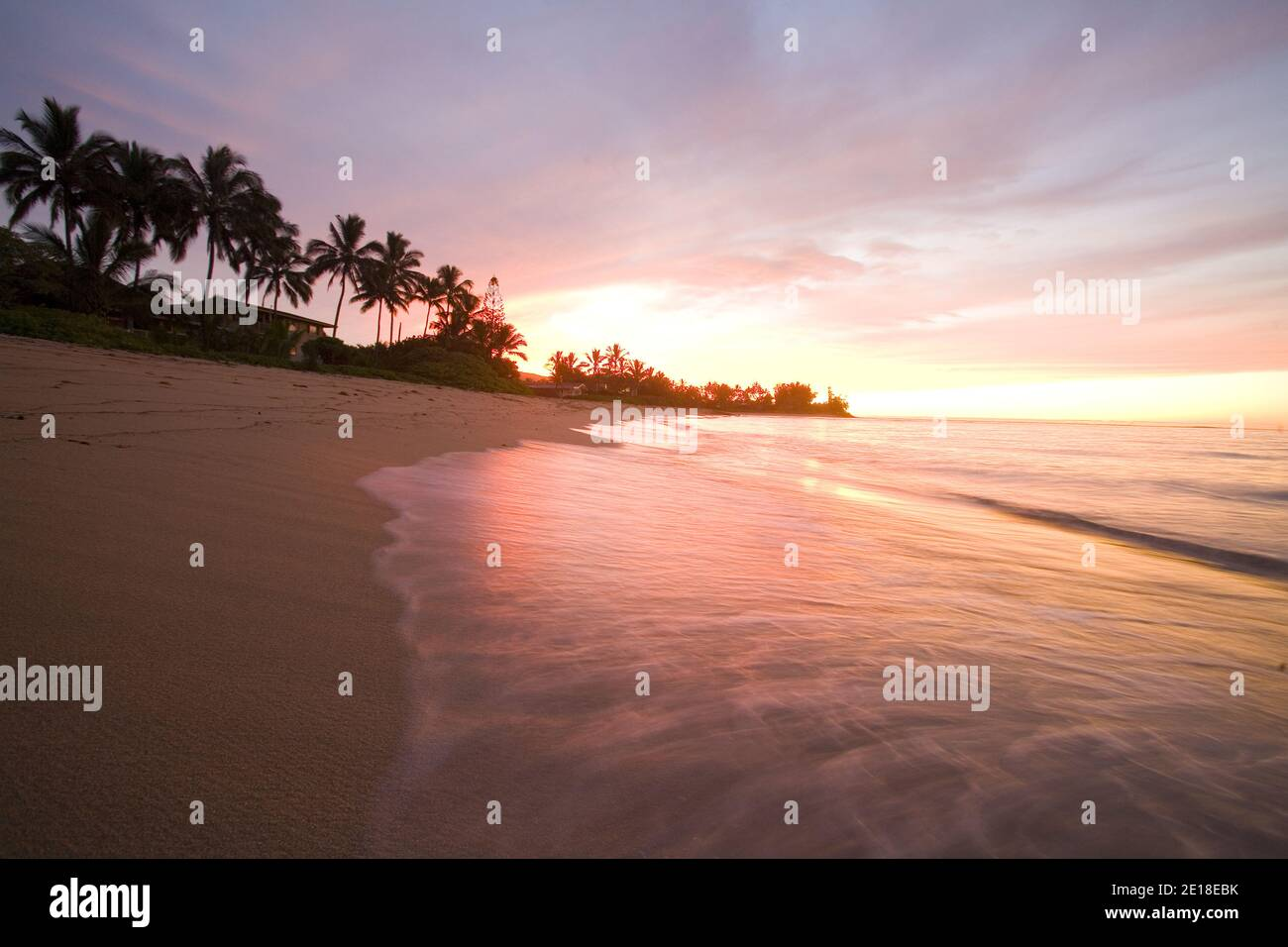 Sunset on Waialua Beach, with calm waves in foreground Foto de stock