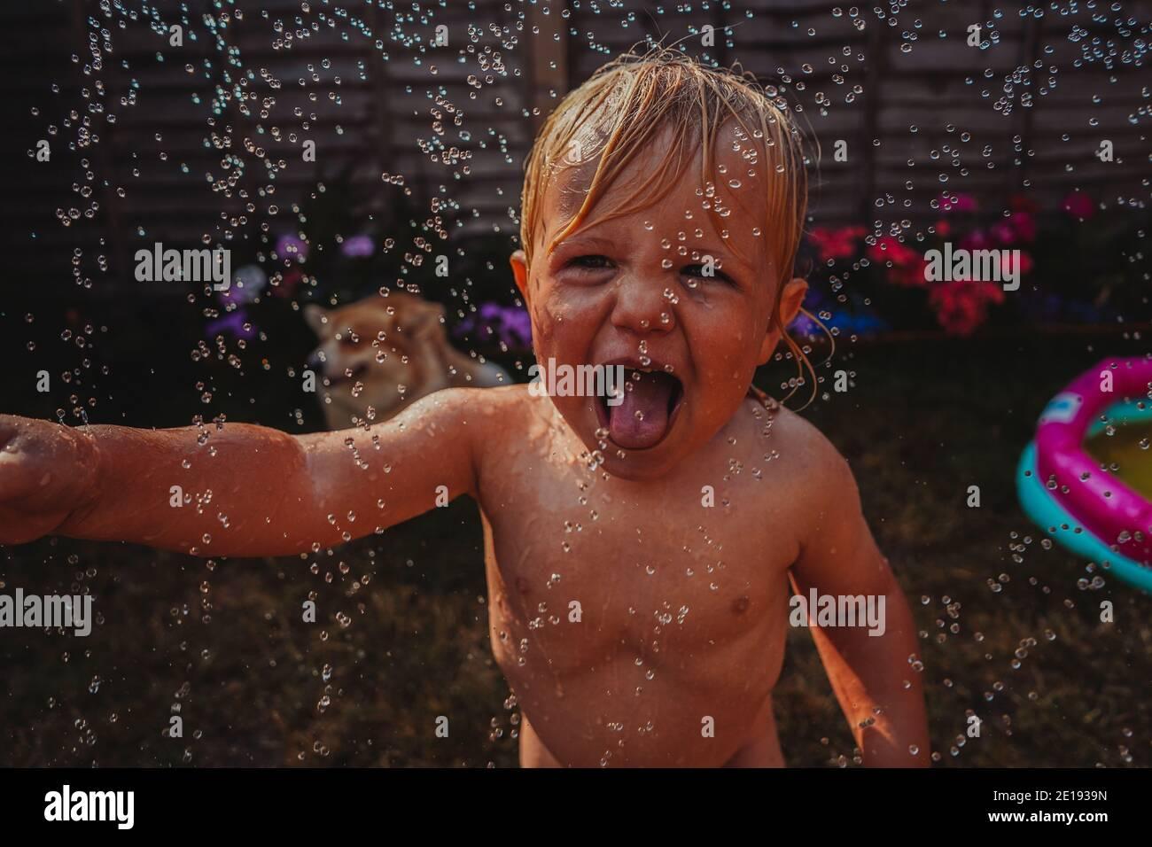 Niño jugando con un rociador en el jardín Foto de stock