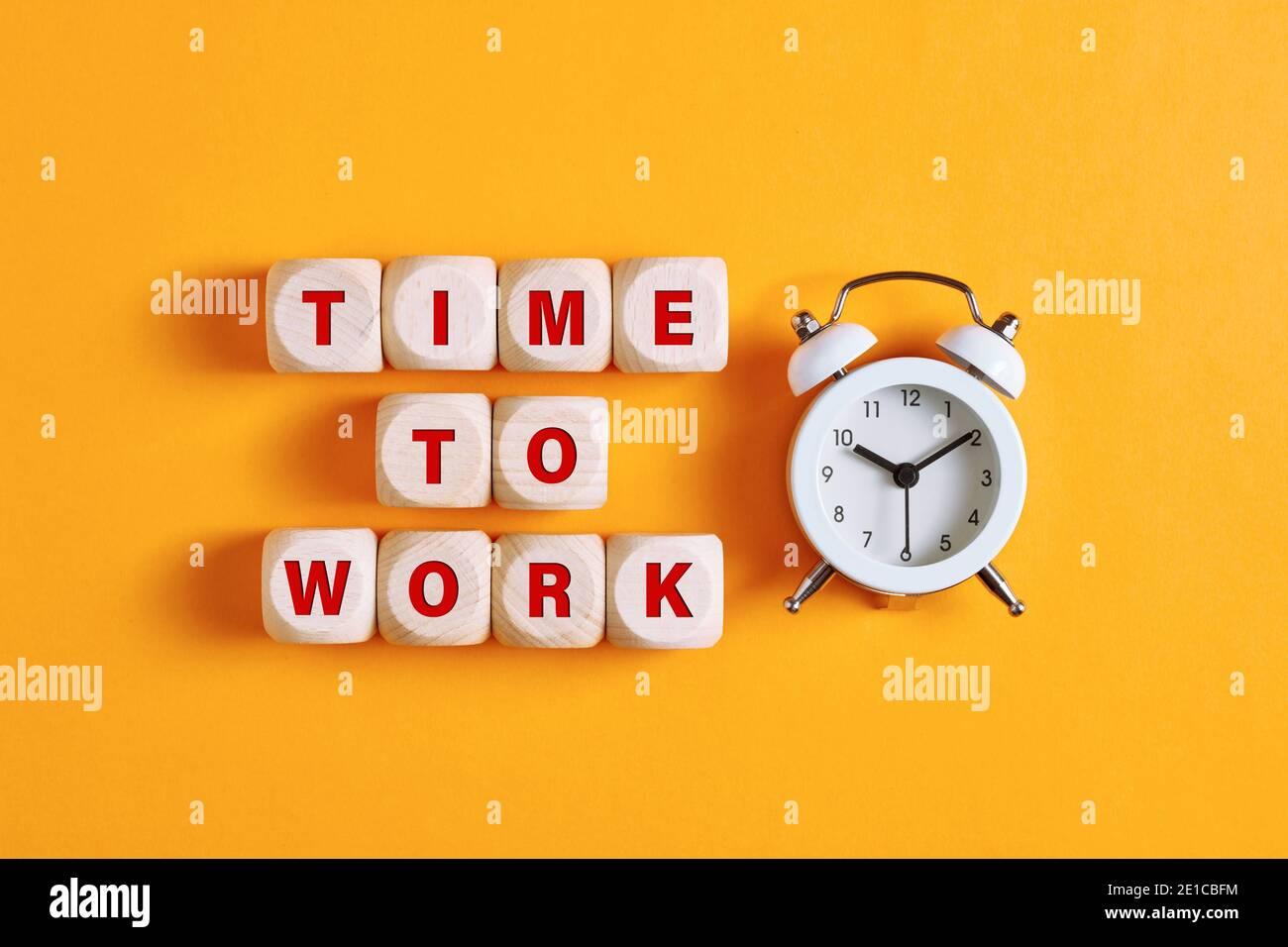 La palabra tiempo para trabajar en cubos de madera con reloj despertador. Negocio, carrera o trabajo duro concepto. Foto de stock