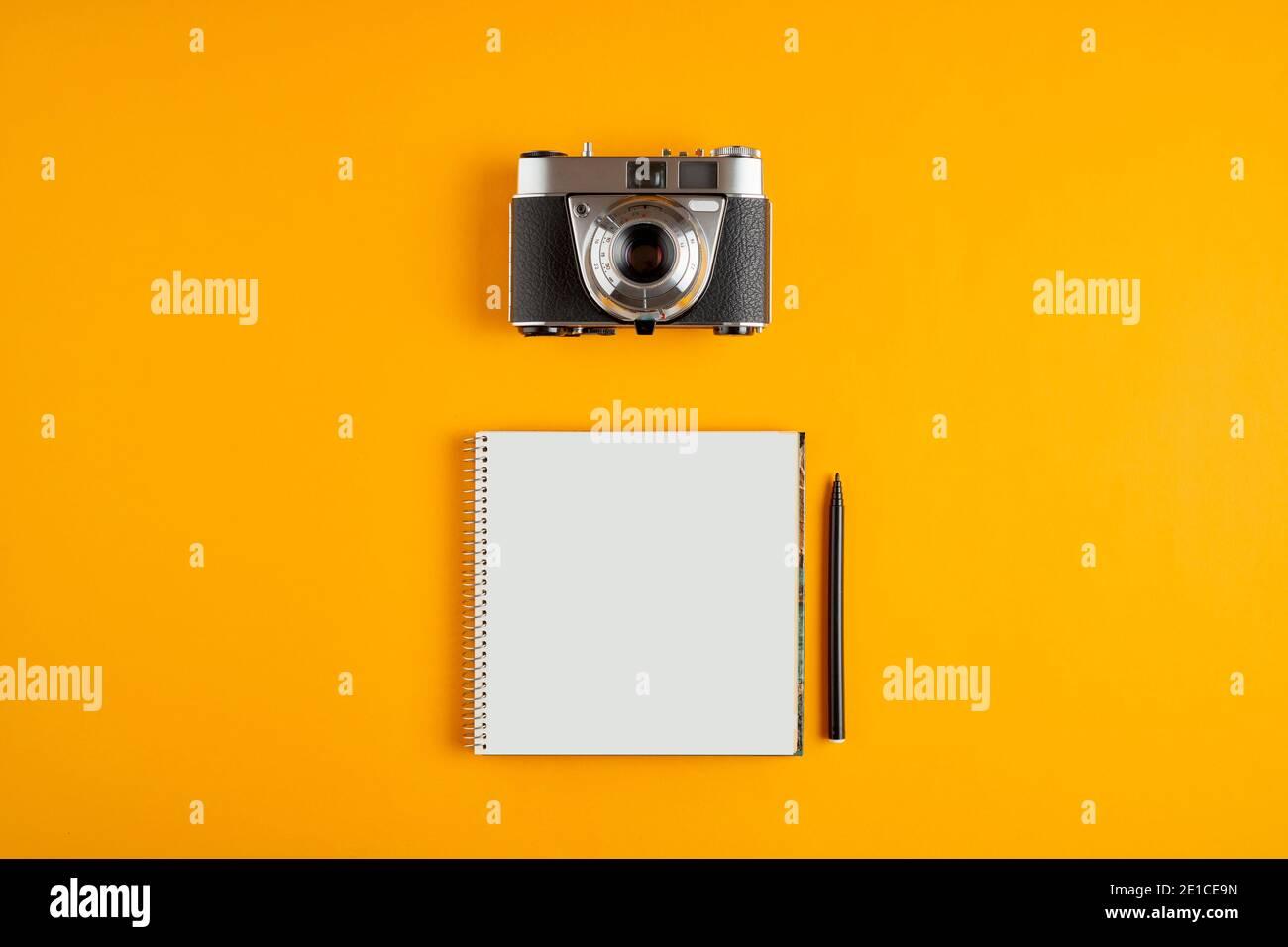 Cámara analógica de época con un cuaderno espiral en blanco sobre fondo amarillo con espacio de copia. Foto de stock