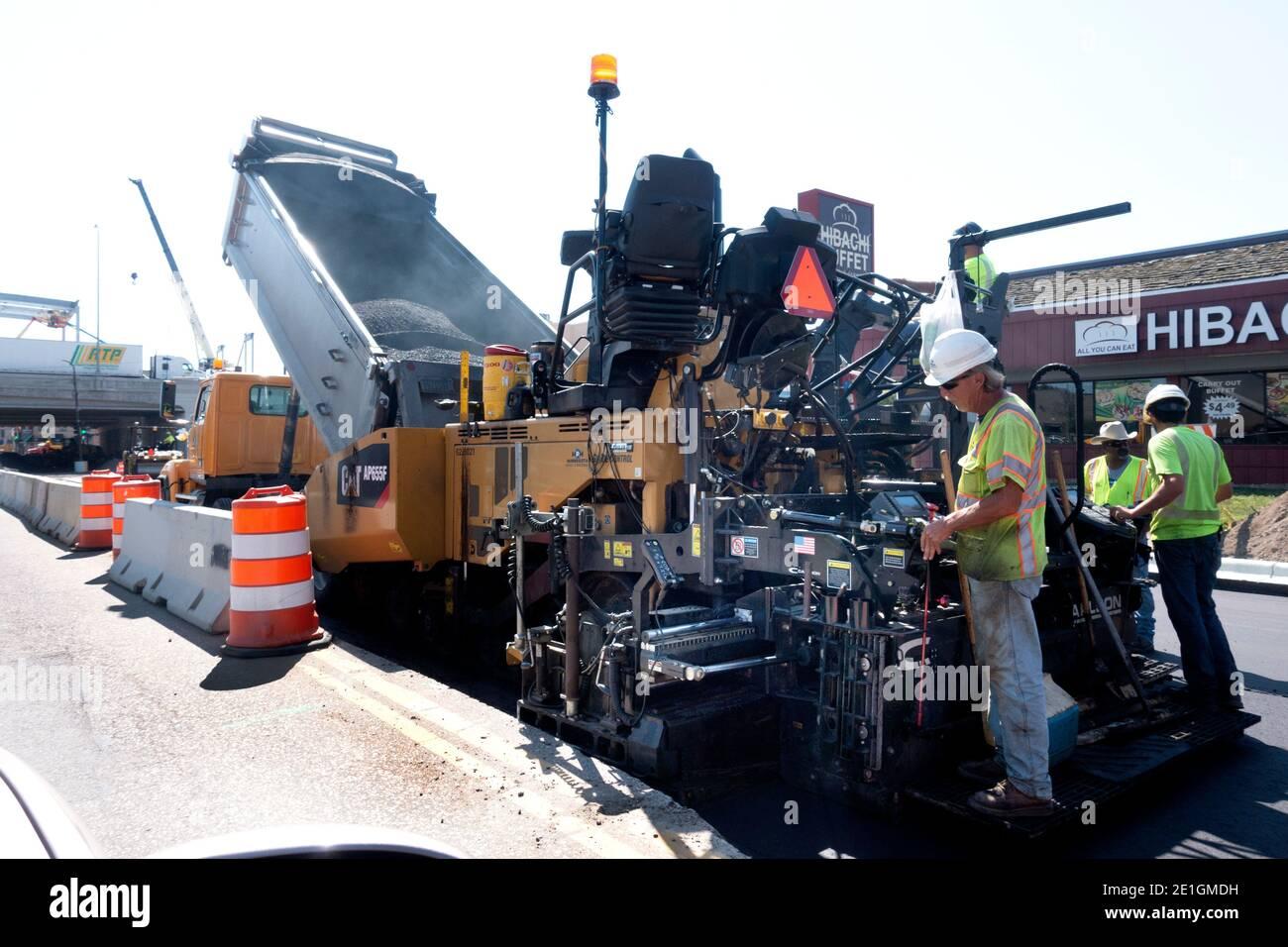 Hombres con camiones y máquinas reparando y repavimentando la calle del lago. Minneapolis Minnesota MN EE.UU Foto de stock