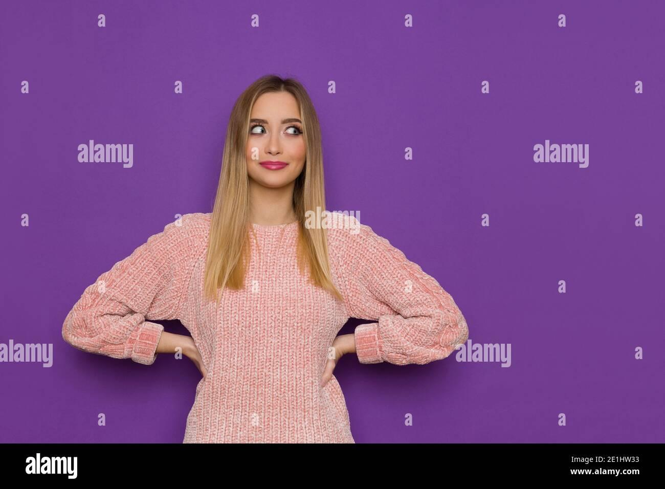 Mujer joven linda en suéter rosa está posando con las manos en la cadera y mirando al lado. Estudio de cintura arriba sobre fondo púrpura. Foto de stock