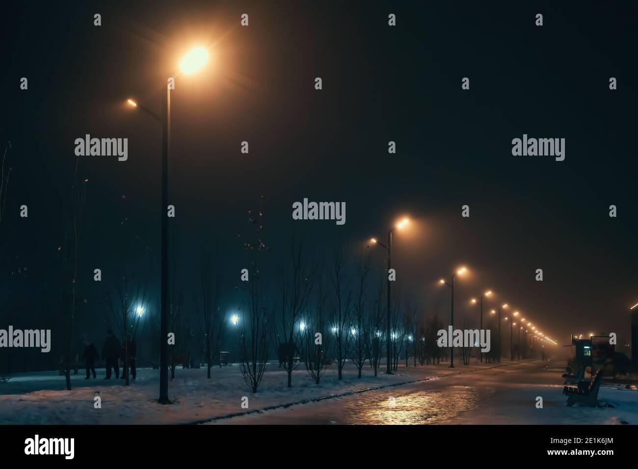 Callejón urbano en la noche de invierno foggy iluminado por las lámparas de la calle. Foto de stock