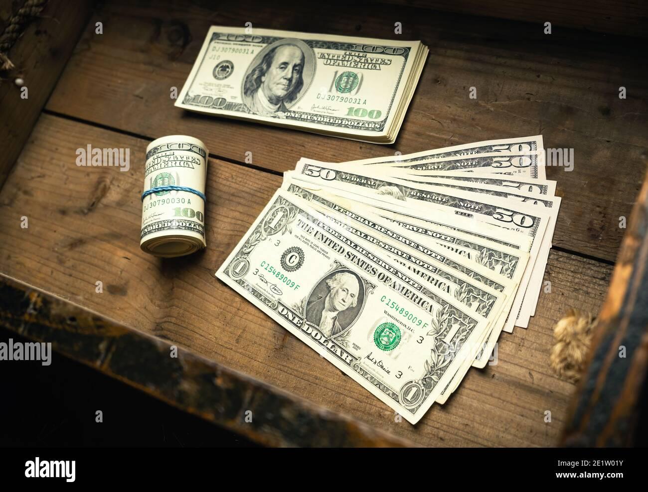 Cantidad de billetes de EE.UU. En pila de dinero y en rollo en cajón de madera. Dinero en efectivo de cientos de dólares, fondo de moneda de papel. Foto de stock