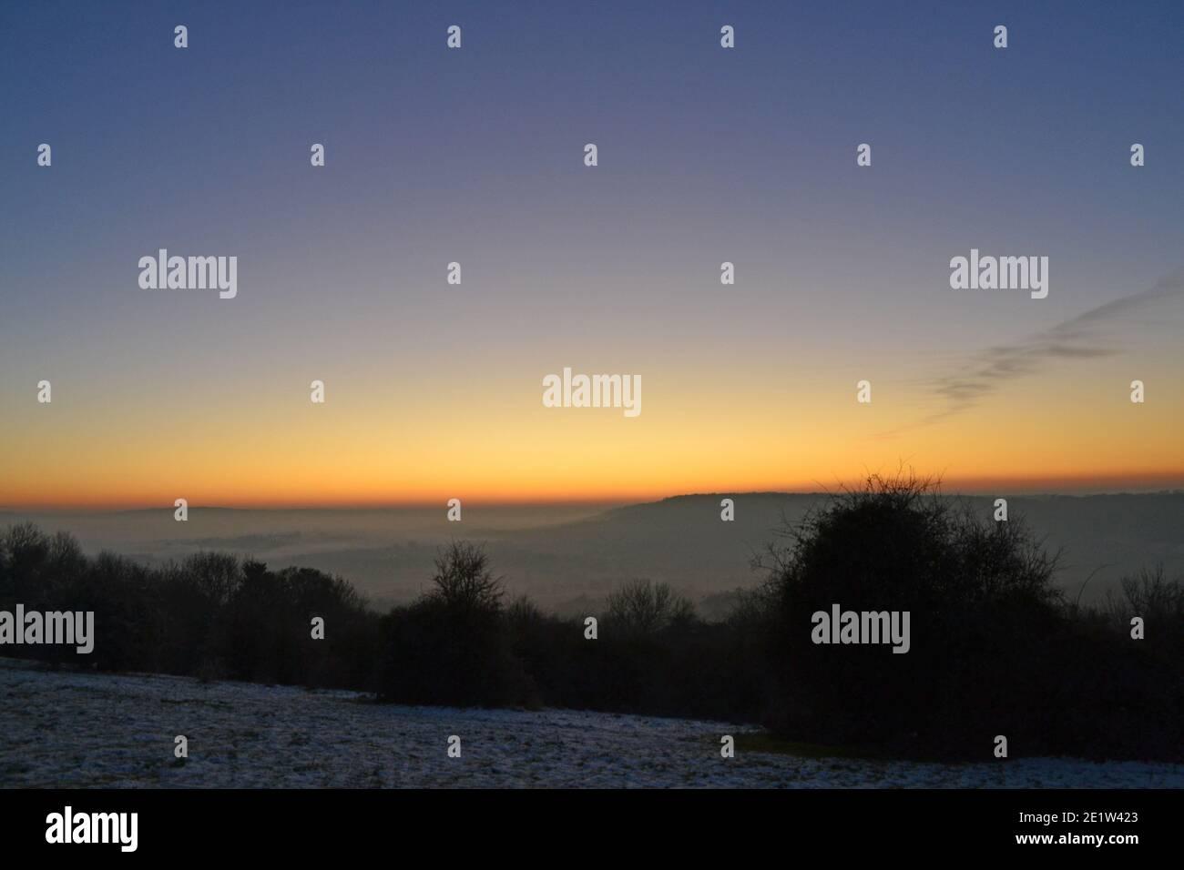 Espectacular puesta de sol en la brumosa luz de invierno en el North Downs, Fackenden Down, en Kent, cerca de Sevenoaks, crujiente, cielo claro sobre el enorme resplandor naranja, cielo azul Foto de stock
