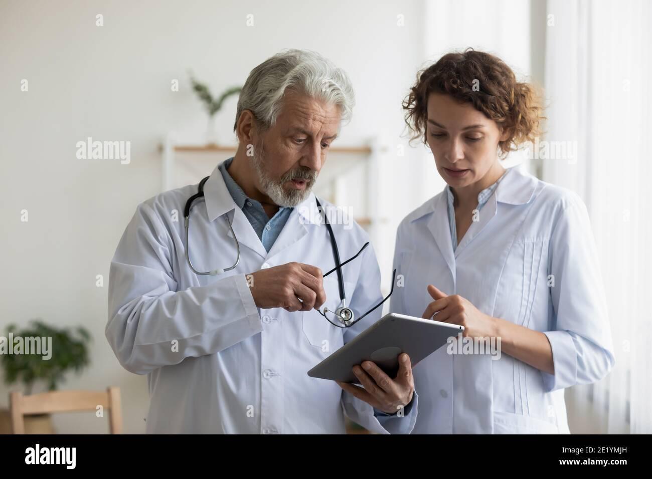 Médico anciano serio que discute los resultados de la prueba con un colega joven. Foto de stock