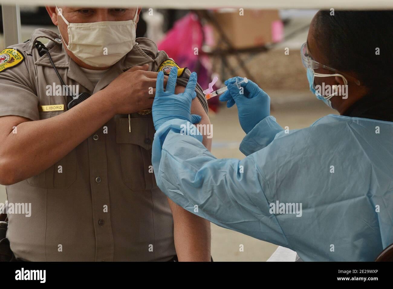 Los Ángeles, California, EE.UU. 13 de enero de 2021. Un guardabosques es inoculado con la vacuna moderna COVID-19 en el sitio de vacunación del Balboa Sports Center en los Ángeles el martes, 12 de enero de 2021. Las personas de 65 años o más y las personas con condiciones de salud graves.subyacentes en los Ángeles y en toda California podrían ser rápidamente elegibles para una vacuna COVID-19, con funcionarios federales que instan a los estados el martes a distribuir más ampliamente las vacunas. Foto de Jim Ruymen/UPI crédito: UPI/Alamy Live News Foto de stock