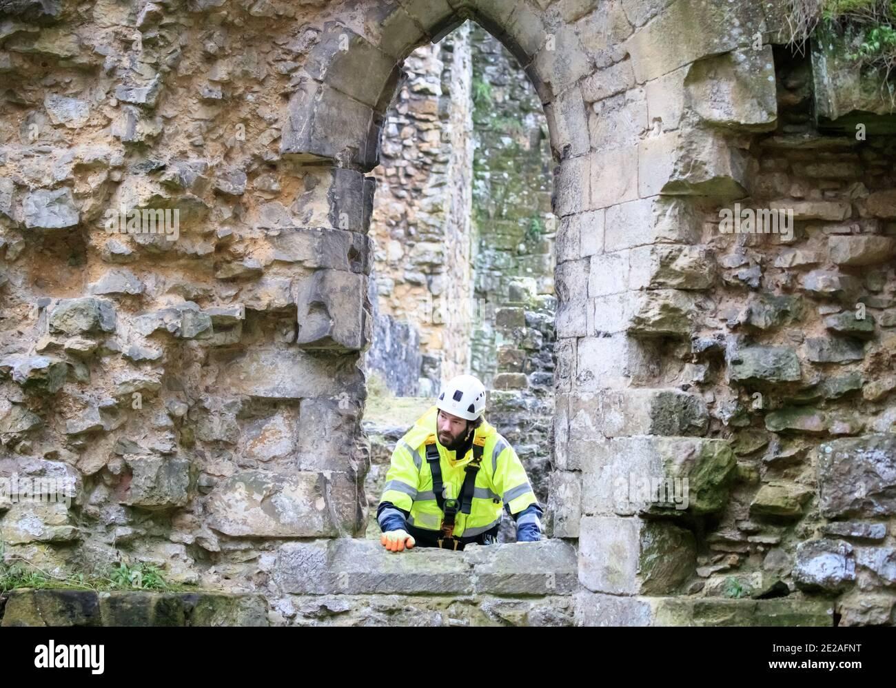 El masón de piedra James Preston de SSH Conservation, examina la Abadía de Rievaulx en North Yorkshire mientras el Patrimonio Inglés se prepara para llevar a cabo un trabajo vital de conservación. El Patrimonio Inglés comisiona una encuesta en la Abadía de Rievaulx en un ciclo de cinco años para evaluar la condición de la abadía desde el nivel del suelo hasta la parte superior de la estructura. Foto de stock
