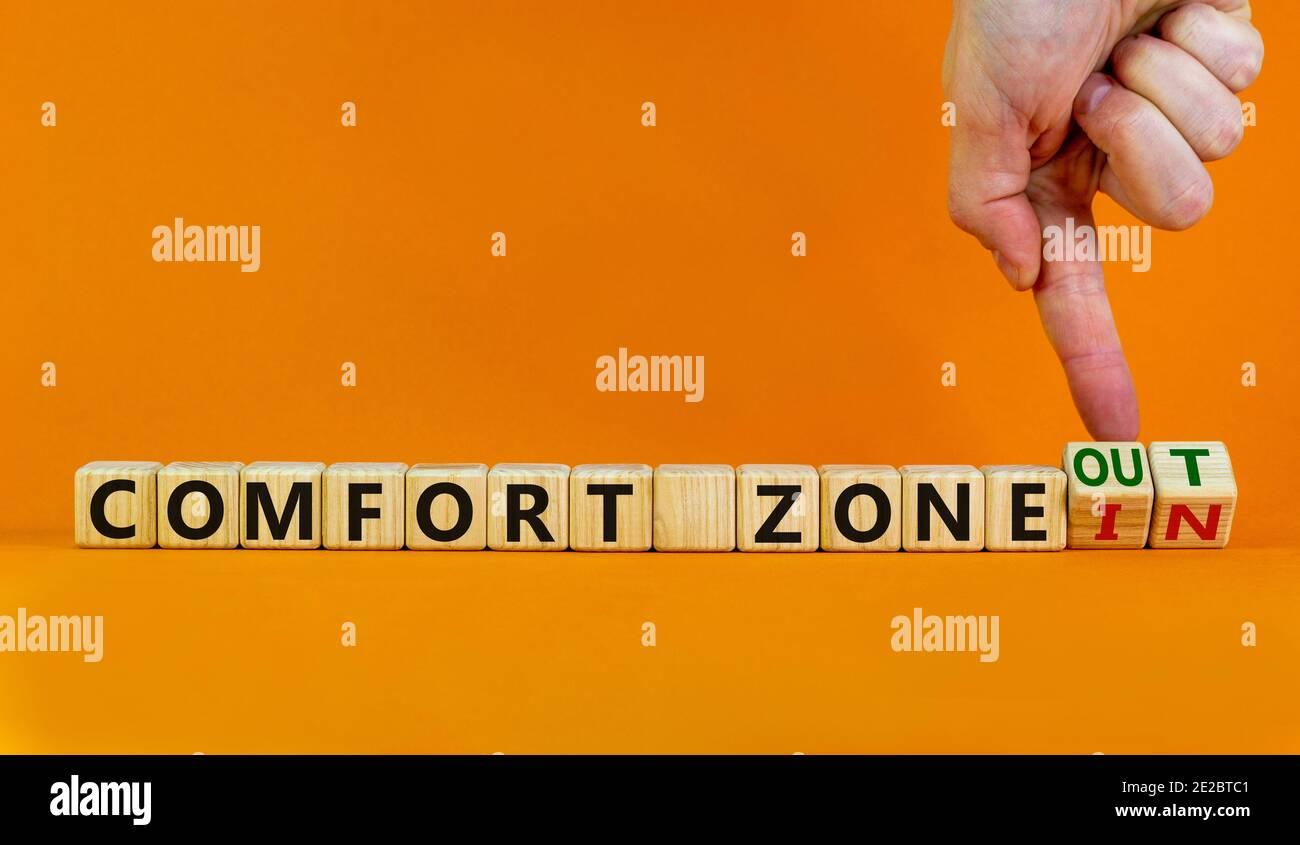 """Símbolo de zona de confort. La mano da vuelta a cubos de madera y cambia las palabras """"en la zona de confort"""" a """"fuera de la zona de confort"""". Hermoso fondo naranja, copia sp Foto de stock"""
