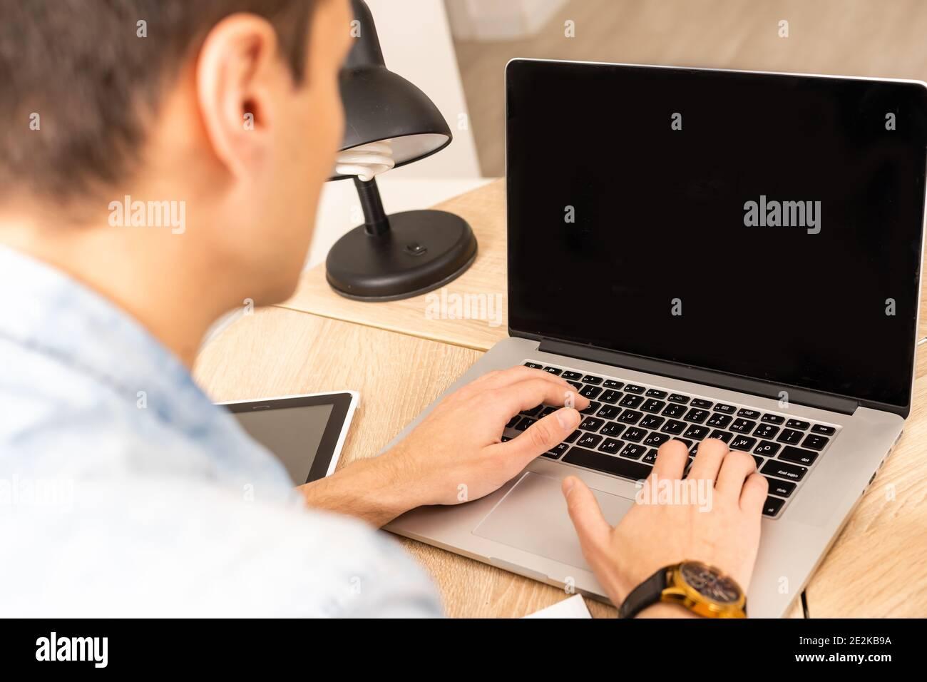 Un joven empresario centrado en la realización de una videollamada con los clientes en el ordenador portátil. Hombre milenario concentrado en gafas dando clases educativas en línea Foto de stock