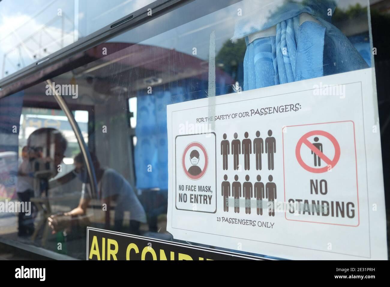 Un letrero colocado fuera del jeepney moderno recuerda a los pasajeros a practicar distanciamiento social mientras que dentro del vehículo, Quezon City. Los jeepneys modernos ahora pueden viajar, pero dentro de rutas seleccionadas. Metro Manila, Filipinas. Foto de stock