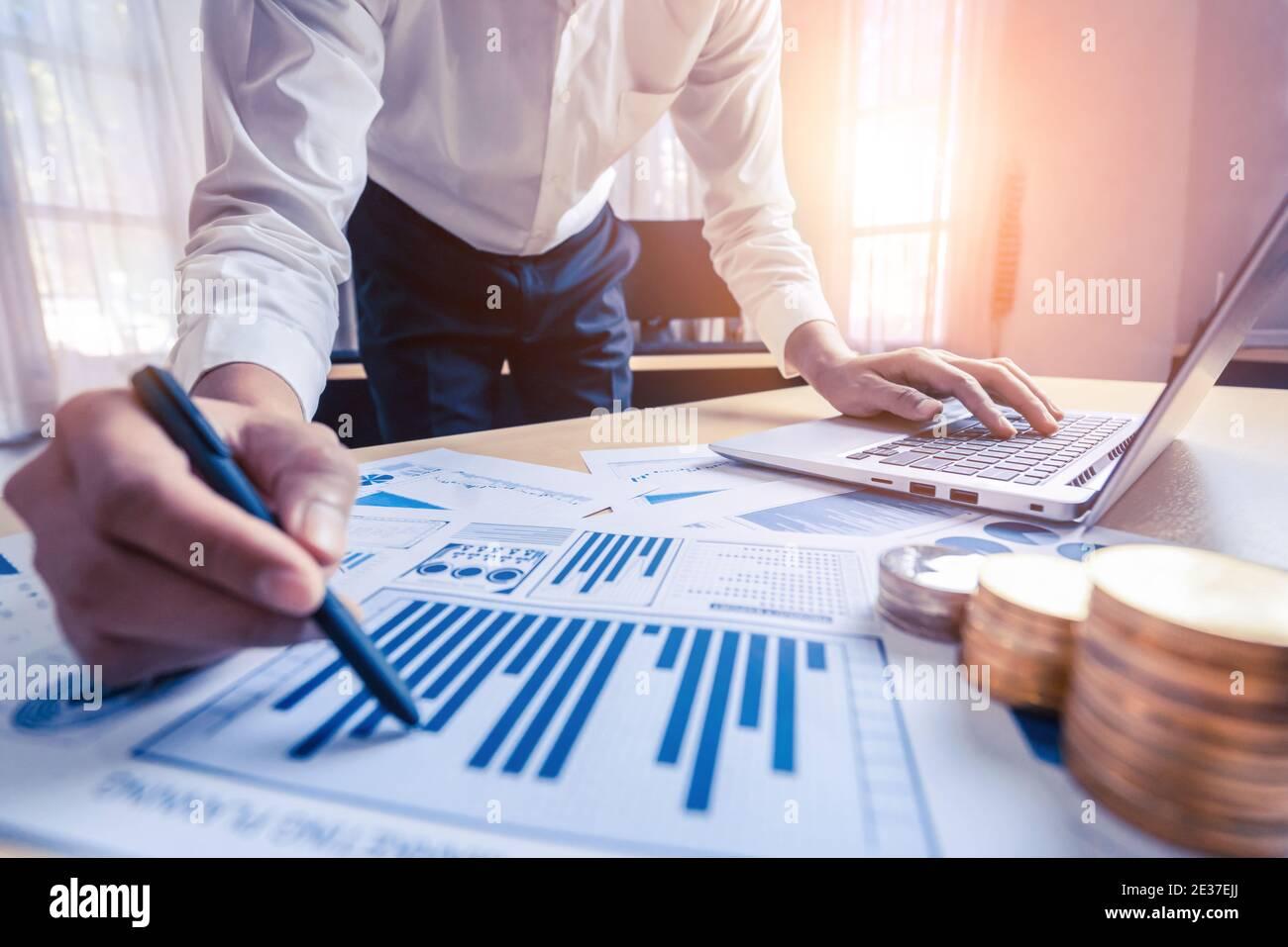 El contador de negocios o el experto financiero analizan el gráfico de informes de negocios y el gráfico de finanzas en la oficina corporativa. Concepto de economía financiera, banca Foto de stock