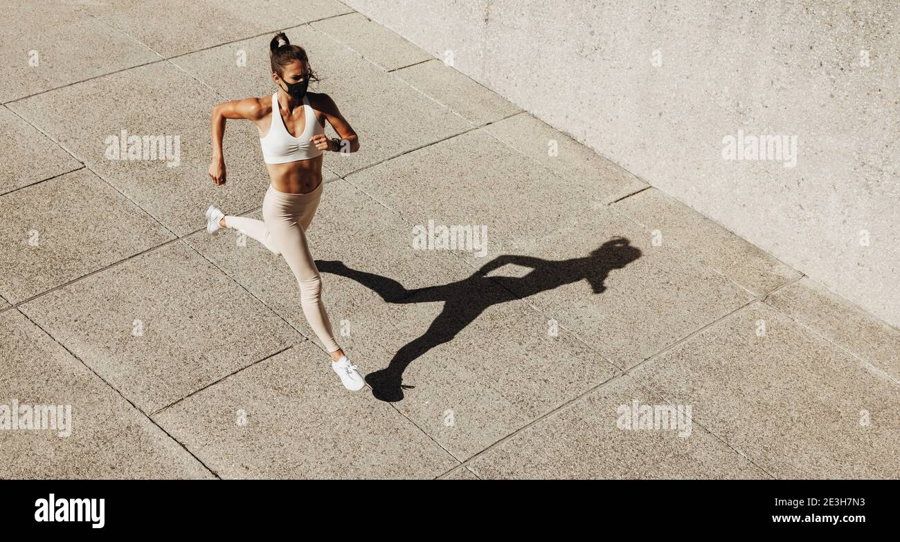 Vista en ángulo alto de una mujer que lleva una máscara facial que se enjuaga al aire libre. Mujer corriendo haciendo ejercicio al aire libre usando una máscara protectora. Foto de stock