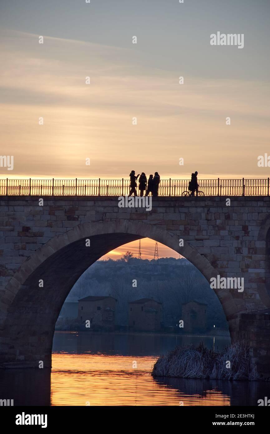 Gente caminando en un puente de piedra al atardecer y los árboles congelados en invierno a la hora dorada. Arcos de piedra, reflejo del sol en el río. Alcantarillas Foto de stock