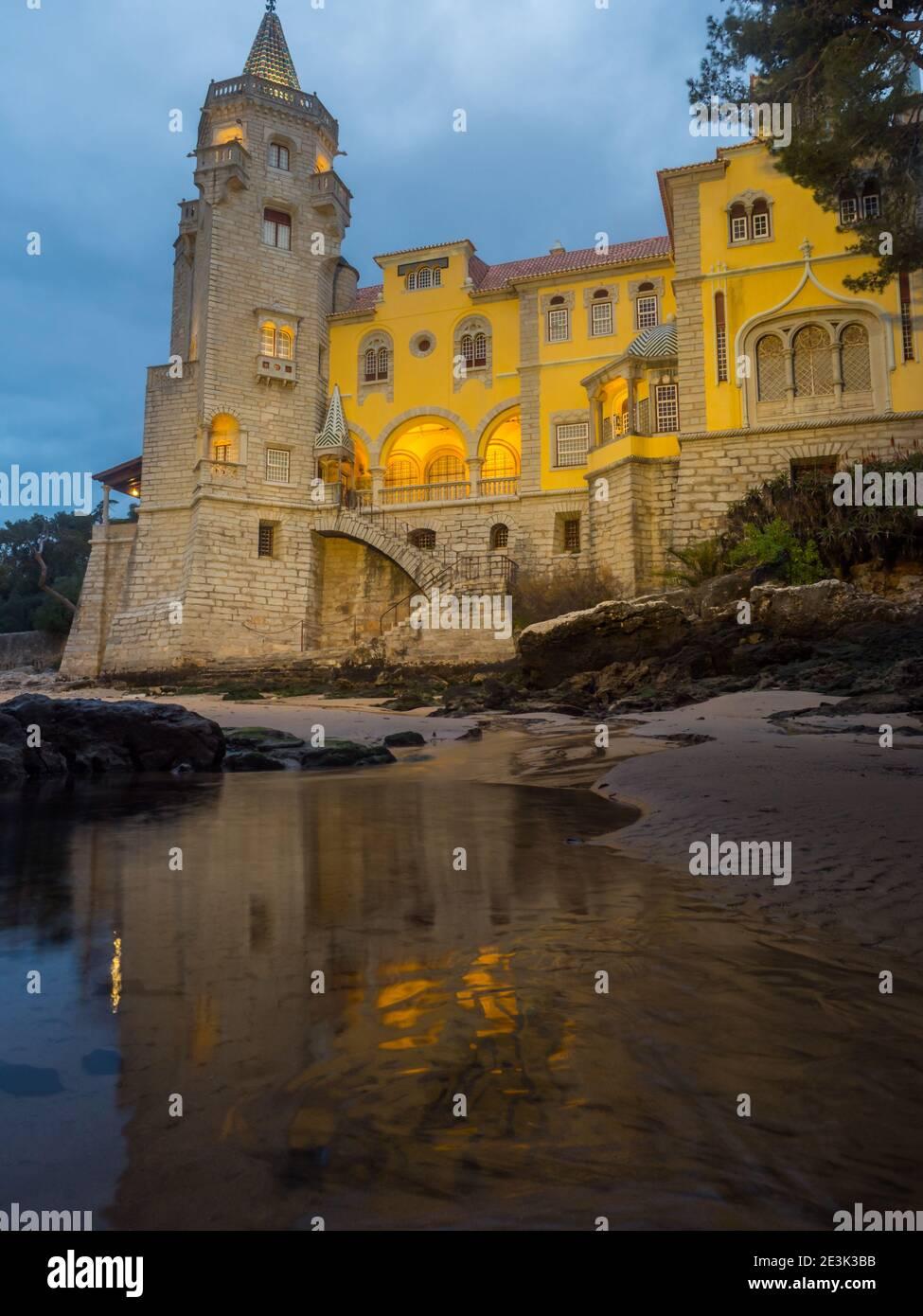 Hermoso edificio del museo - Condes de Castro Guimarães - durante el amanecer con iluminación nocturna, Cascais, Portugal Foto de stock