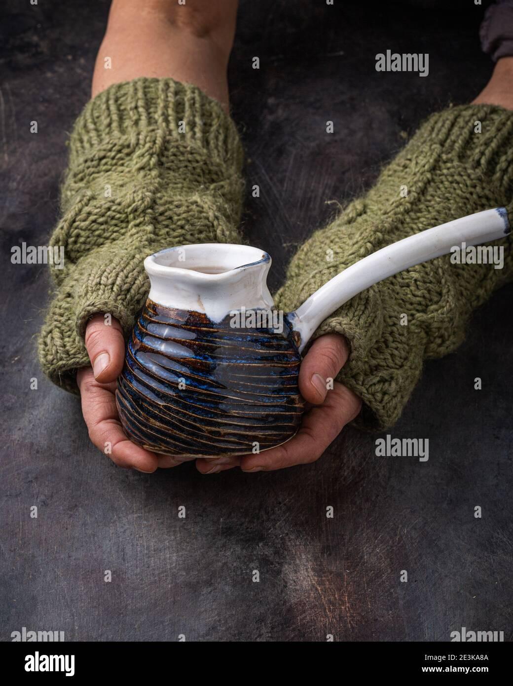 Taza hecha a mano en manos femeninas, foto oscura. Foto de stock