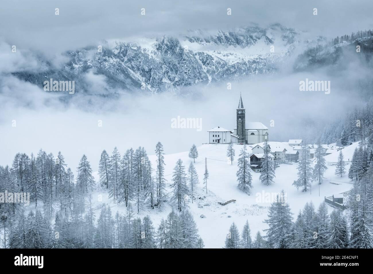 Italia, Véneto, provincia de Belluno, Rocca Pietore, Agordino, el pueblo de laste en invierno con la iglesia de San Gottardo en la colina, Dolomitas Foto de stock